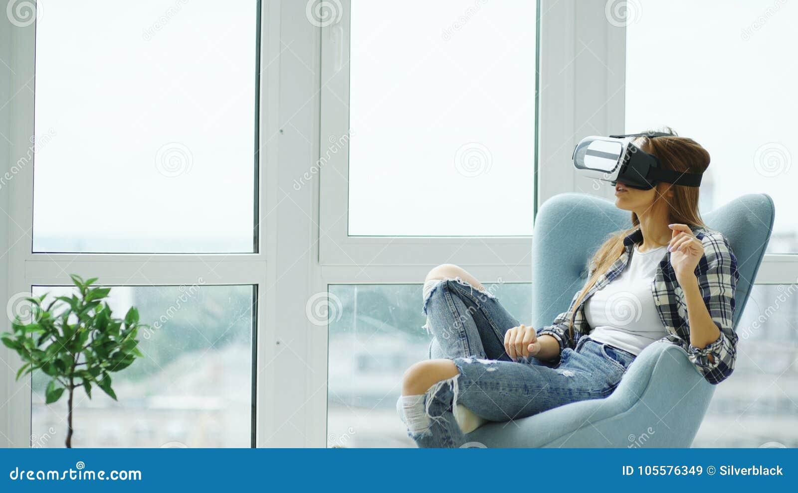La giovane donna ha esperienza di VR facendo uso della cuffia avricolare di realtà virtuale che si siede in sedia sul balcone