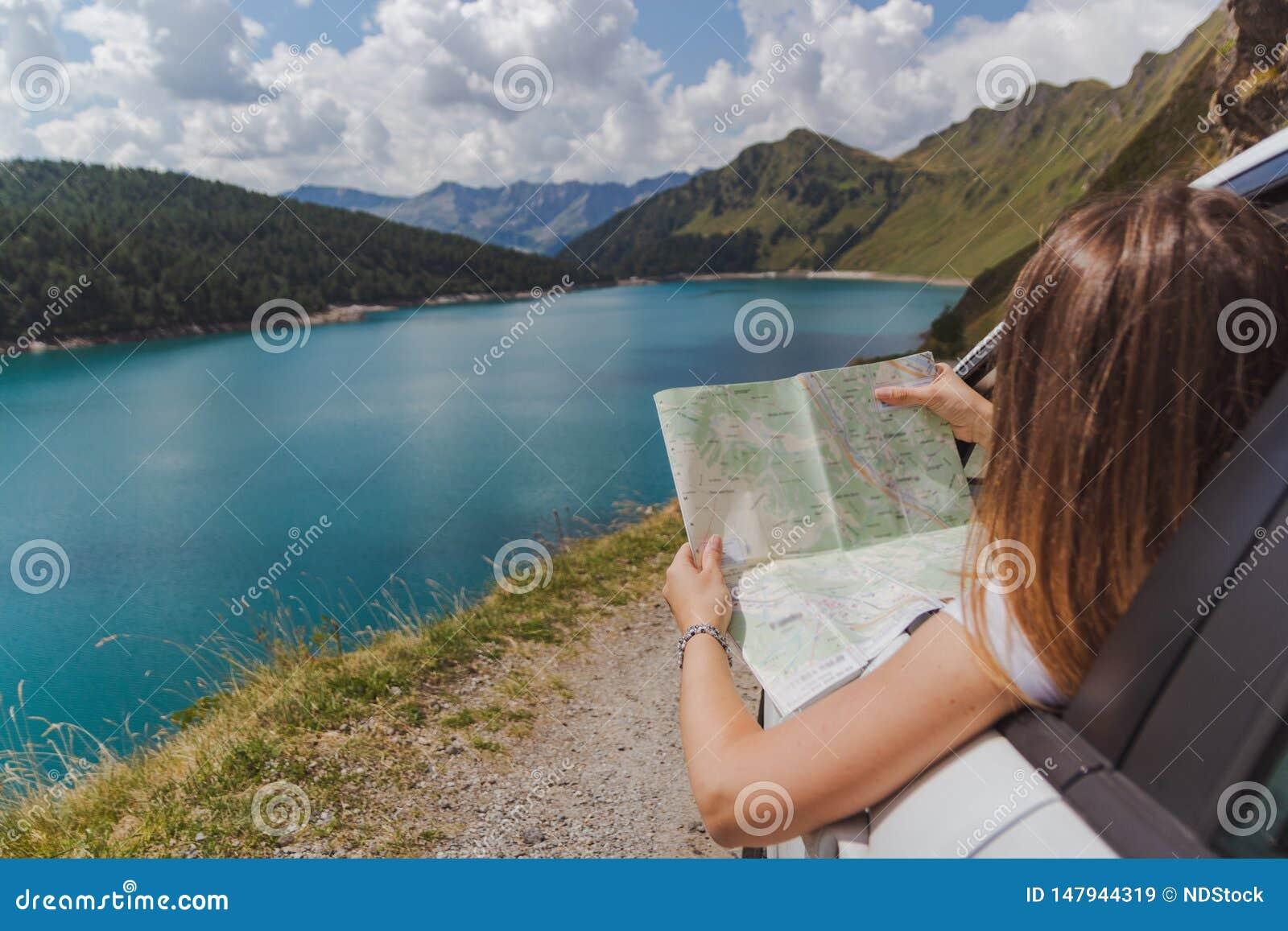 La giovane donna ha perso nelle montagne con la sua automobile che guarda la mappa per trovare la strada giusta