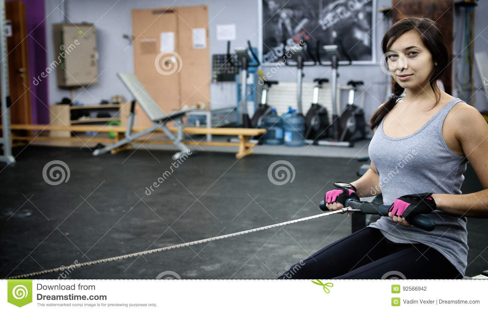 La giovane donna ha su un istruttore per la parte posteriore nella palestra