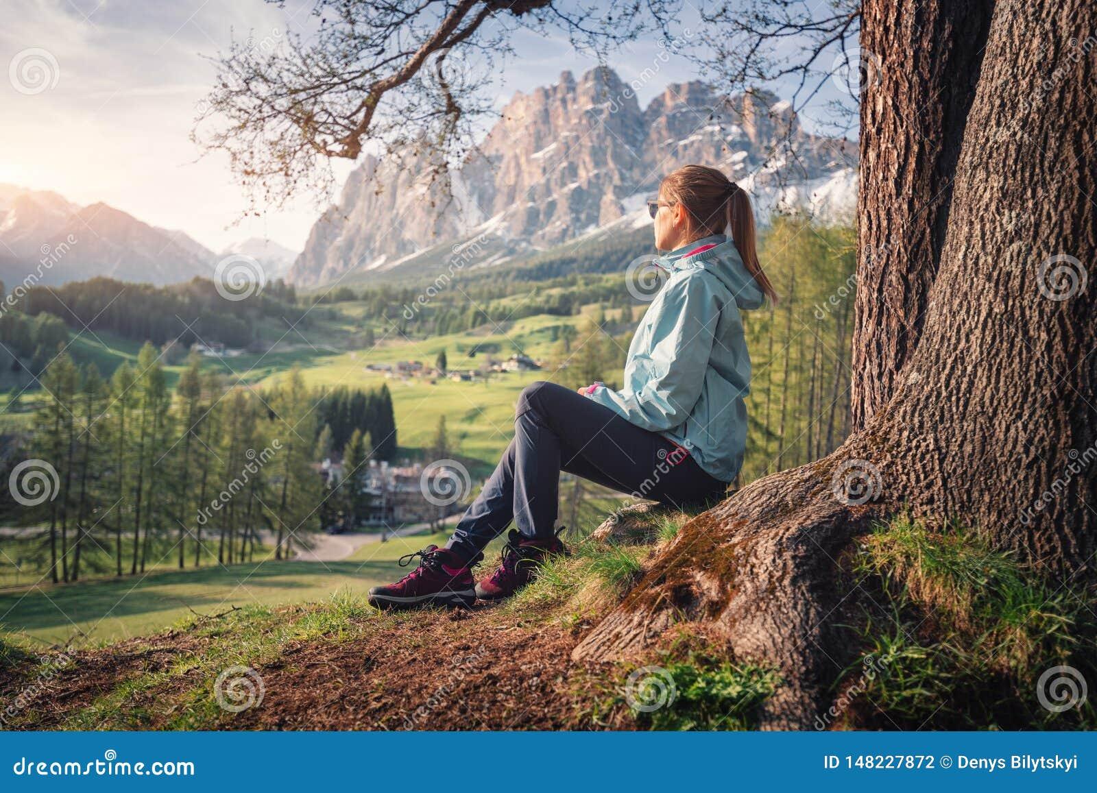 La giovane donna in occhiali da sole e giacca blu sta sedendosi sulla collina