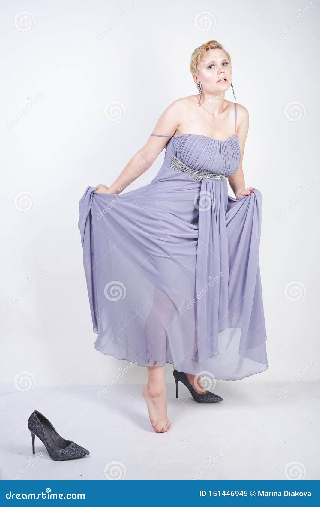 La giovane donna più incantante di dimensione in vestito grigio dall abito ha perso la pantofola su fondo bianco in studio bella