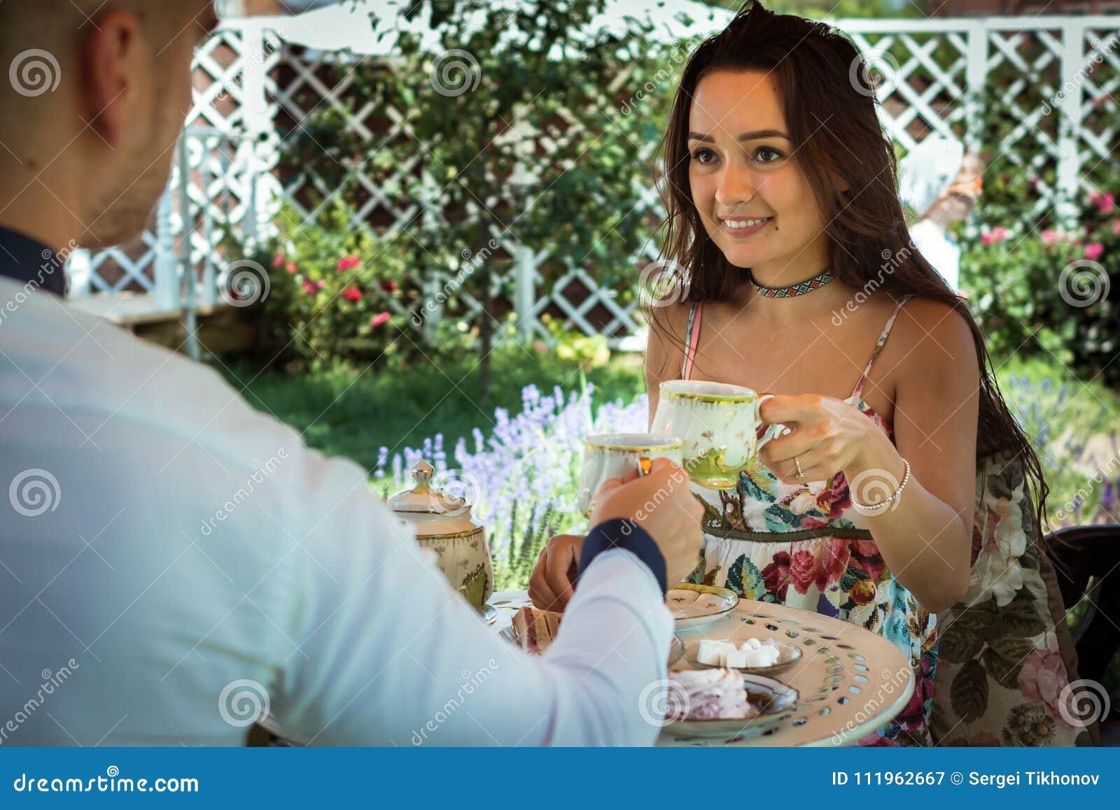 La giovane donna romantica si siede insieme al ragazzo alla tavola