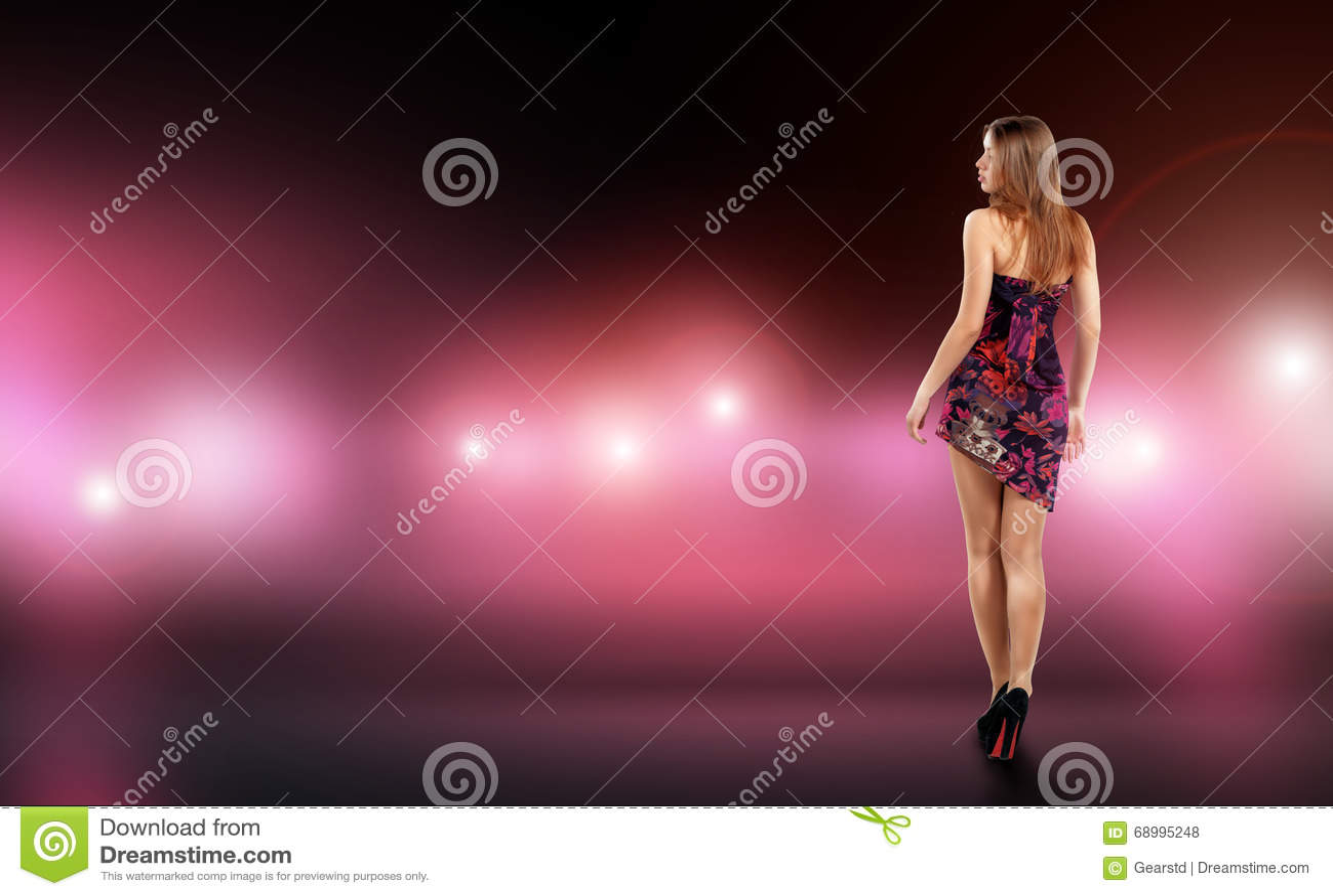 La giovane donna sexy in vestito dal montaggio circondato da cura e la macchina fotografica infiammano Celebrità, modello, stella