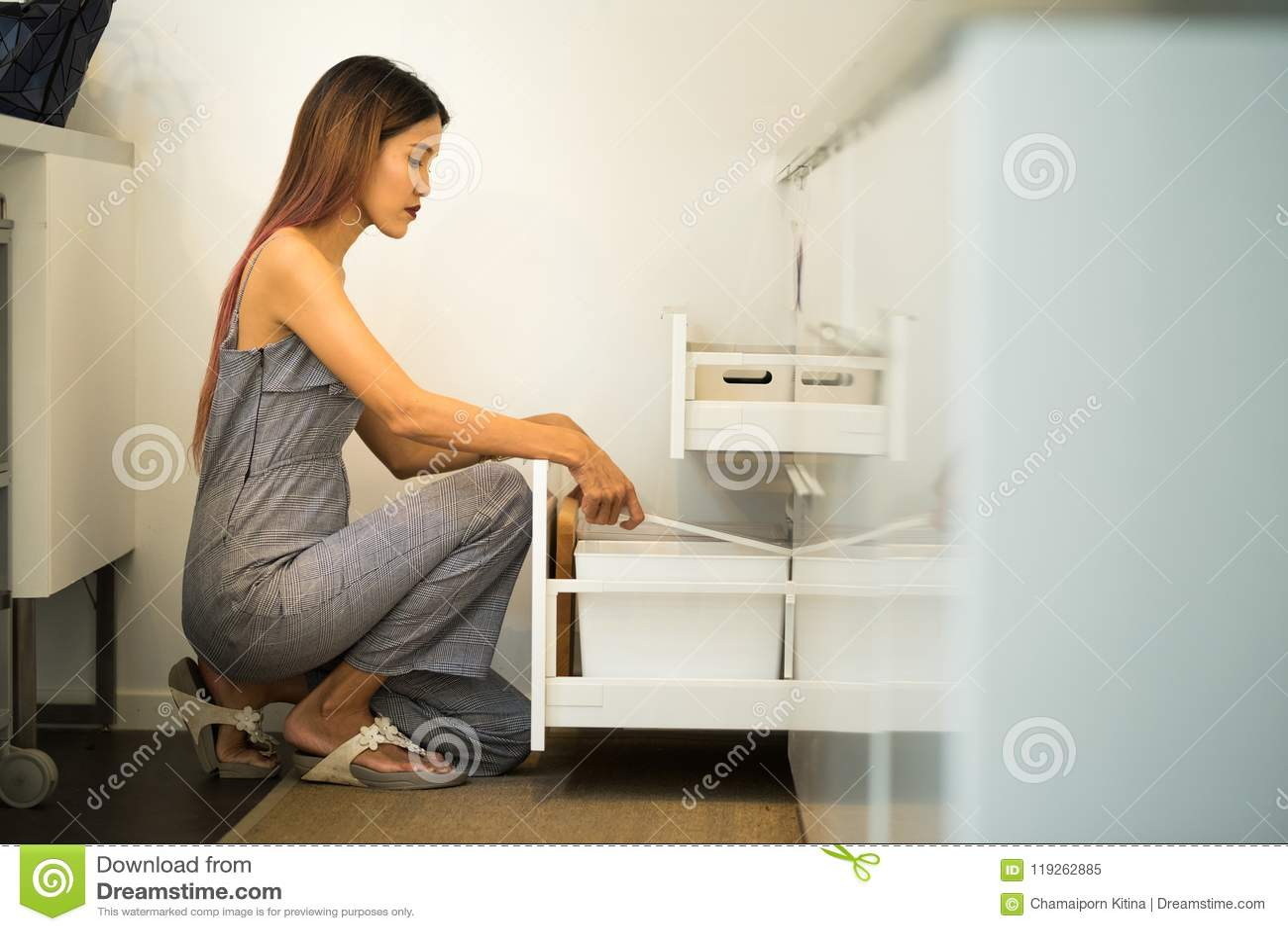 La giovane donna si siede sul ginocchio in suo armadio a giorno della cucina e trova a