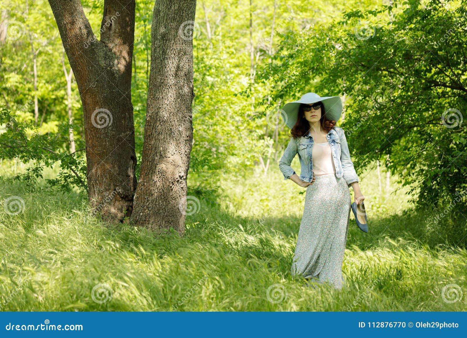 La Giovane Donna Sta Camminando In Un Parco In Cappello Ed ...