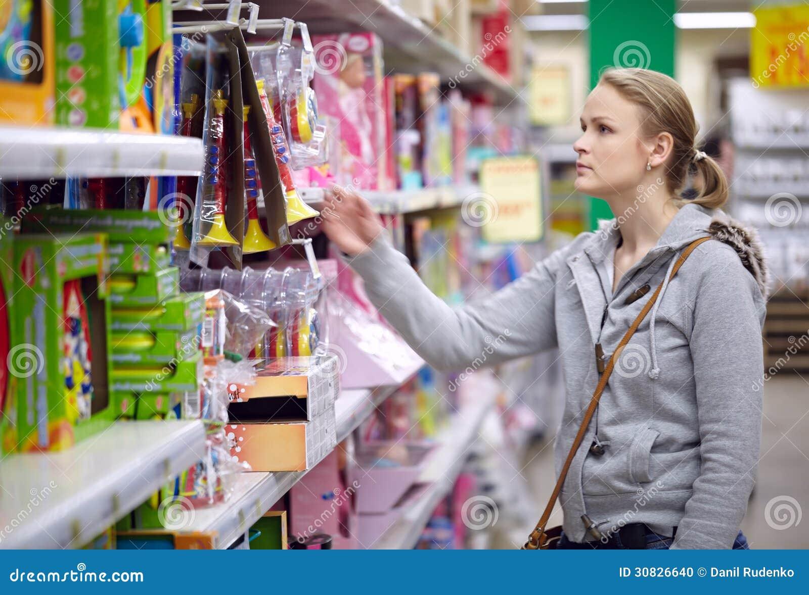 La giovane donna sta scegliendo i giocattoli per il suo bambino.