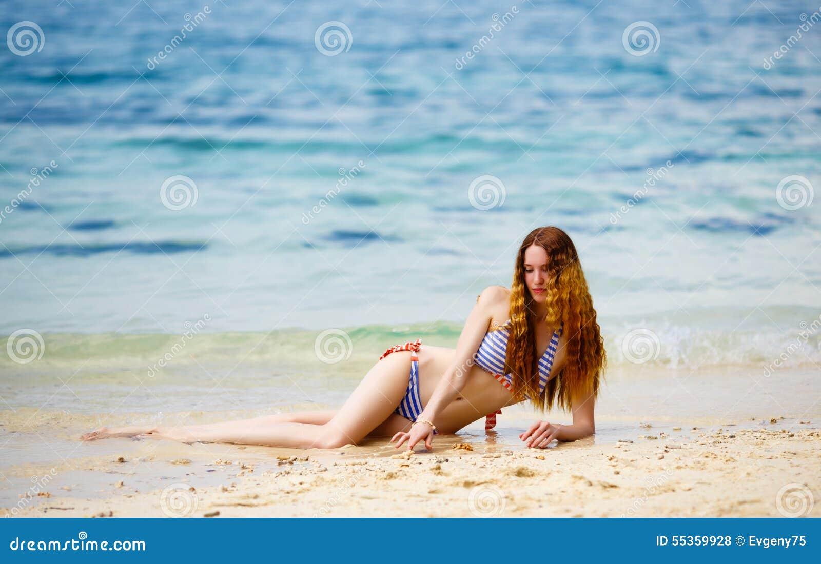 La giovane donna su una spiaggia in bikini