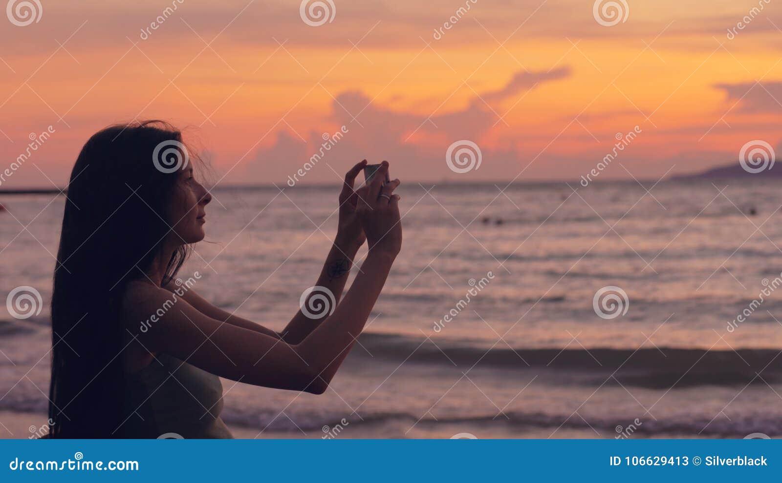 La giovane donna turistica fotografa la vista di oceano con lo smartphone durante il tramonto alla spiaggia