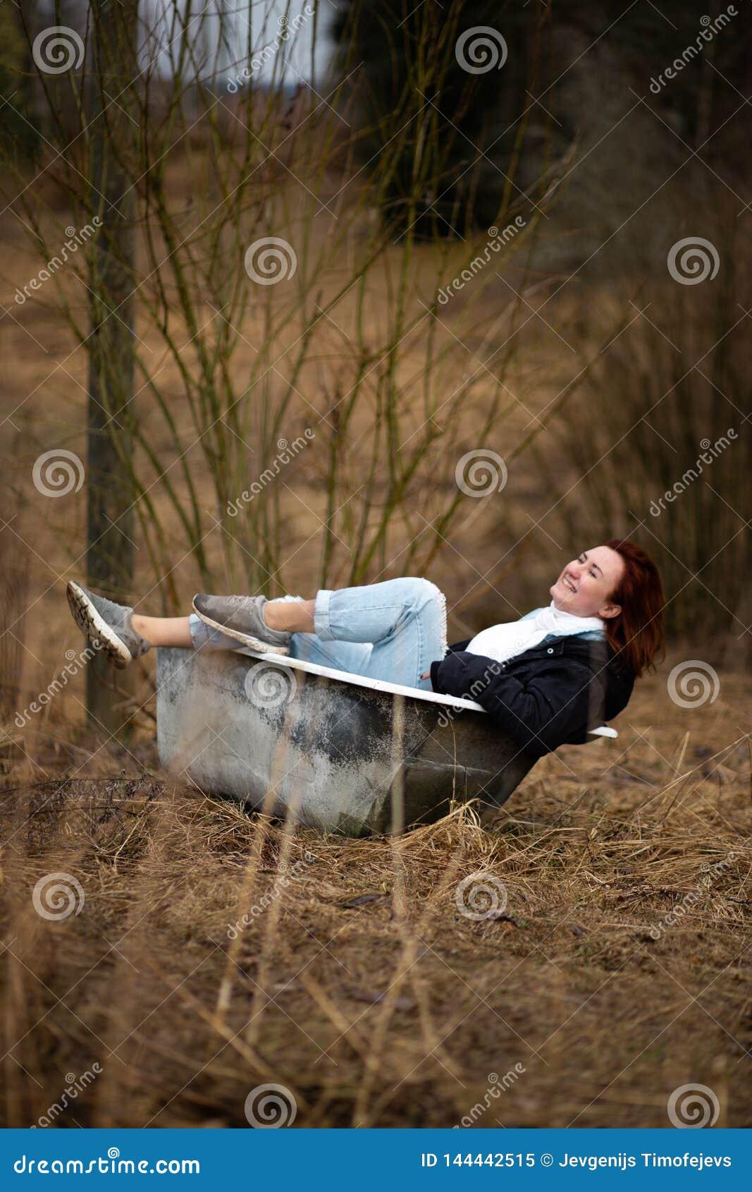 La giovane donna in vestiti sta prendendo un vecchio bagno vuoto in mezzo ad una foresta