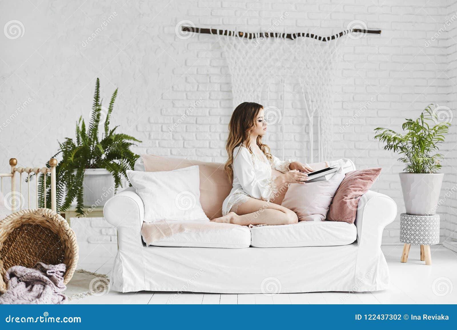 La giovane e bella donna di modello bionda con l ente perfetto in biancheria intima alla moda del raso si siede sul sofà ed a di