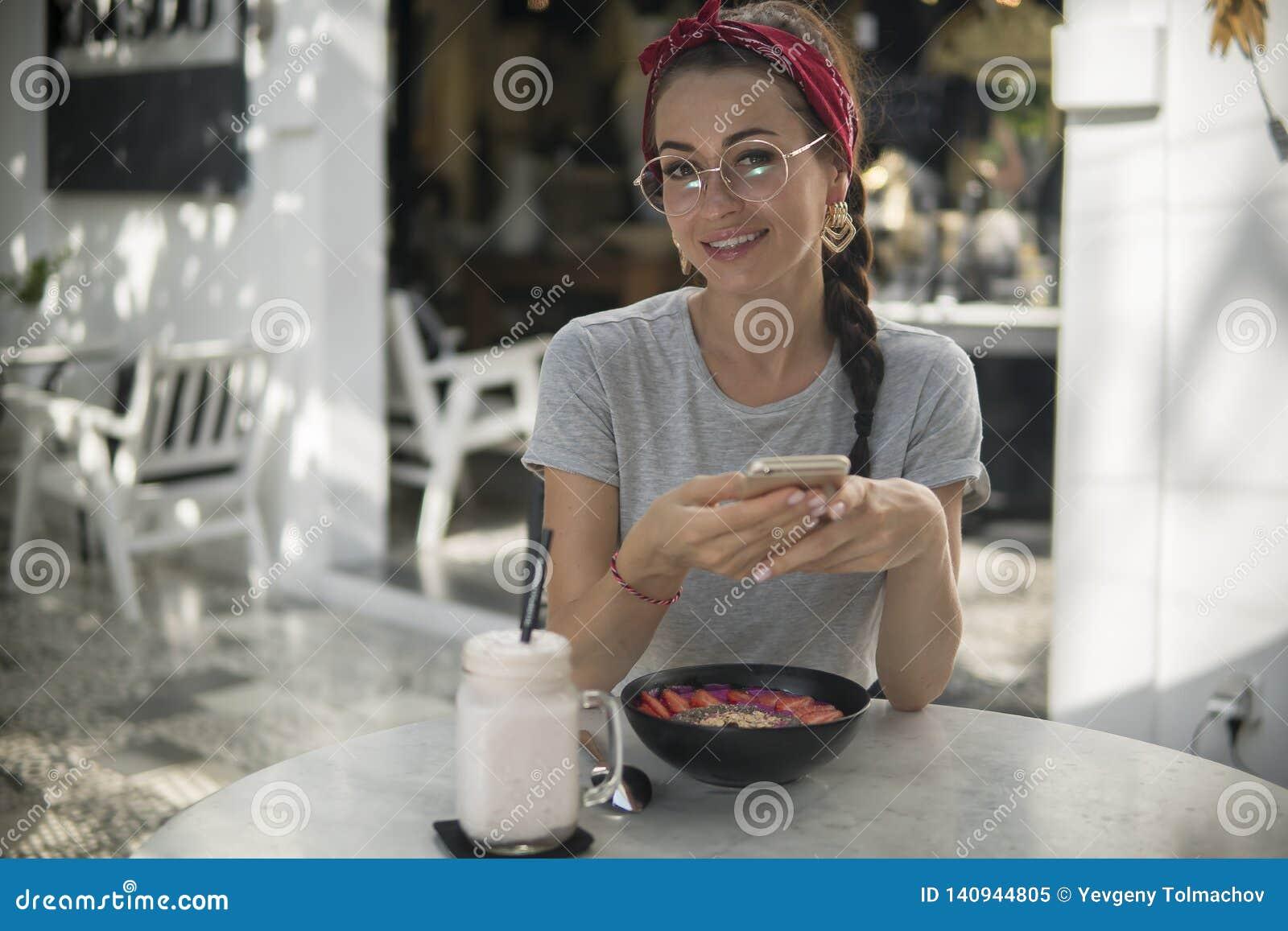 La giovane femmina caucasica felice utilizza il suo telefono quando ha prima colazione in caffè,
