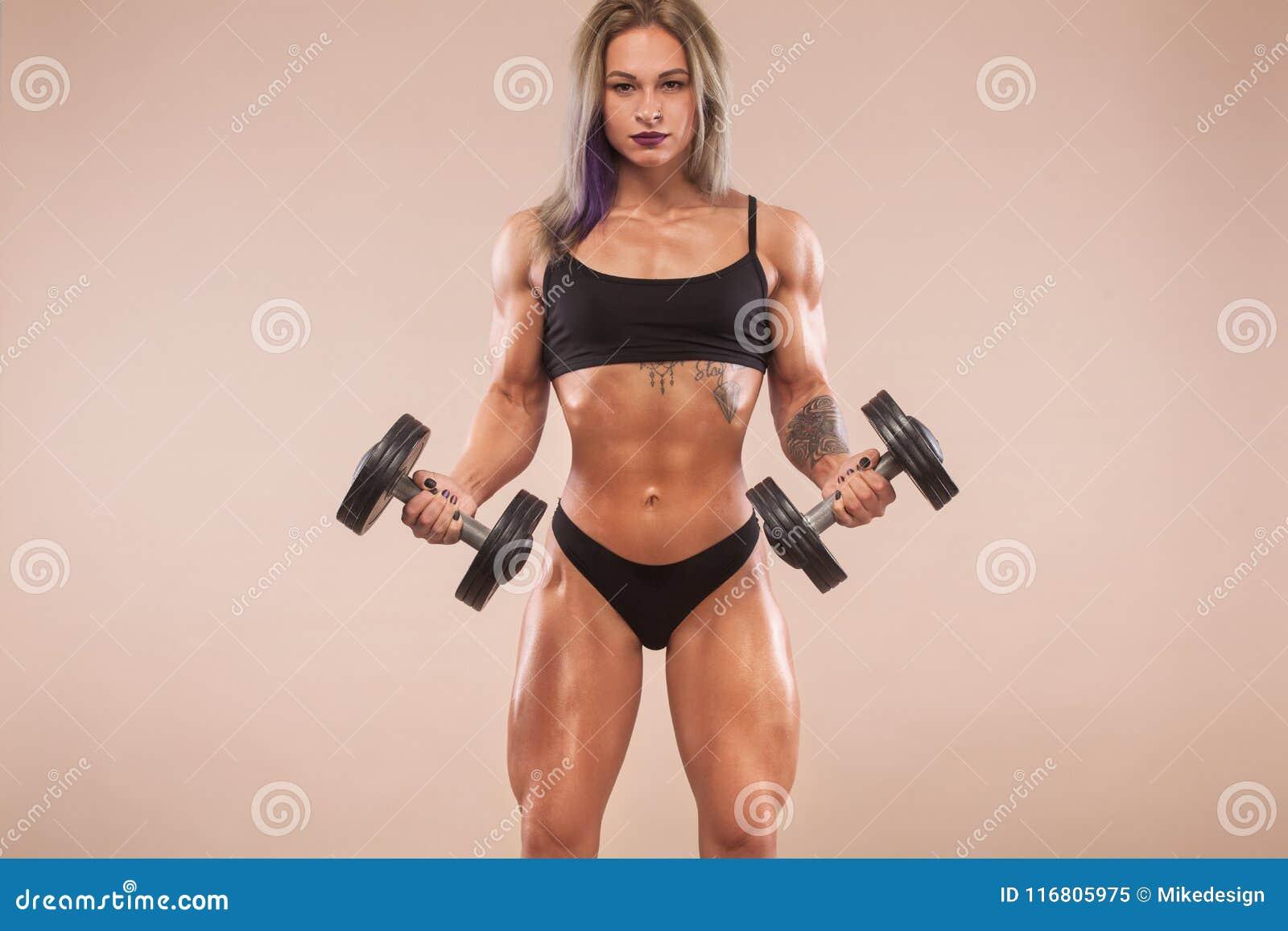 La giovane forma fisica muscolare mette in mostra la donna con il forte ente di misura su fondo leggero