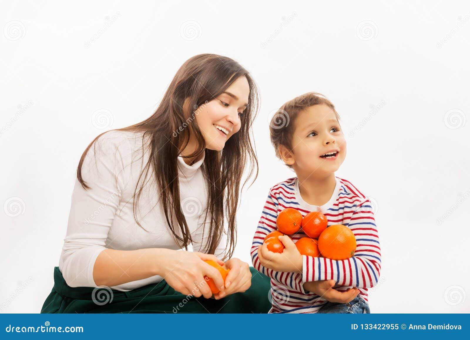 La giovane madre mangia la frutta e le verdure con il suo giovane figlio