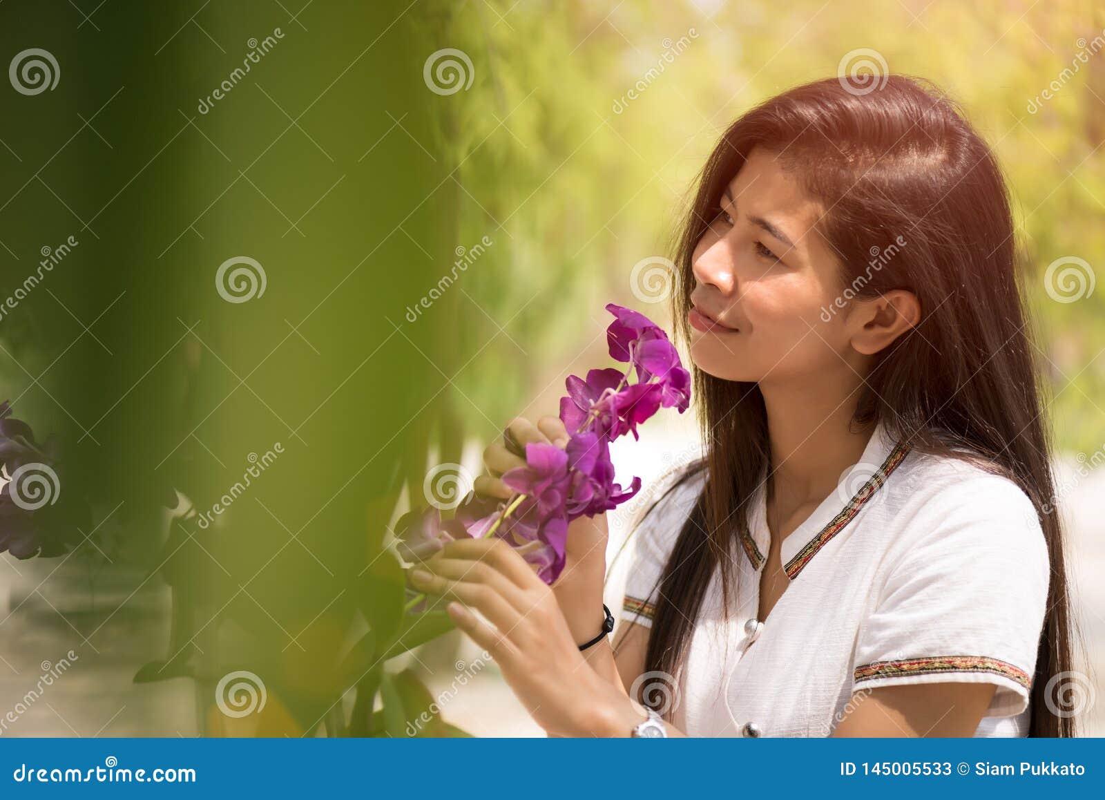 La giovane orchidea asiatica felice della tenuta della donna con un sorriso felice dentro graden