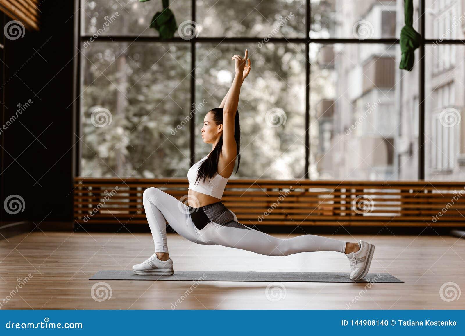 La giovane ragazza mora esile vestita in cima e calzamaglia bianche di sport sta facendo l affondo inverso e raggiungere le armi
