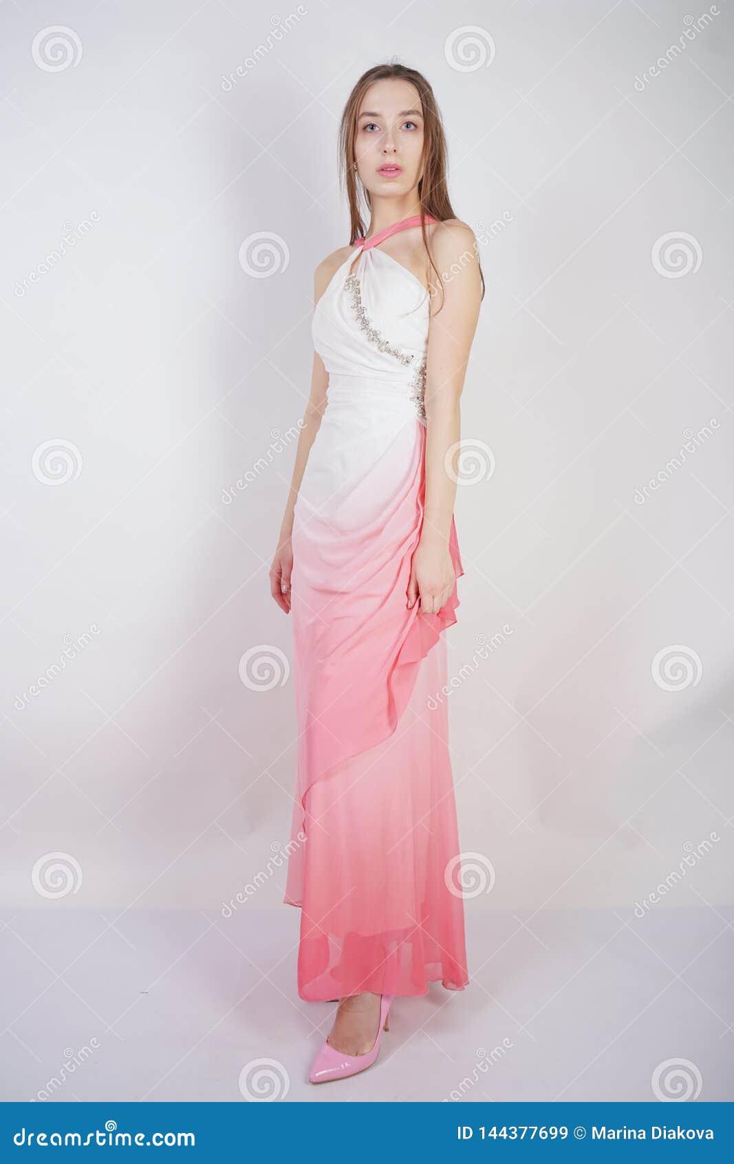 La giovane ragazza teenager sveglia sta in vestito dall estate con Ombre rosa su fondo bianco in studio