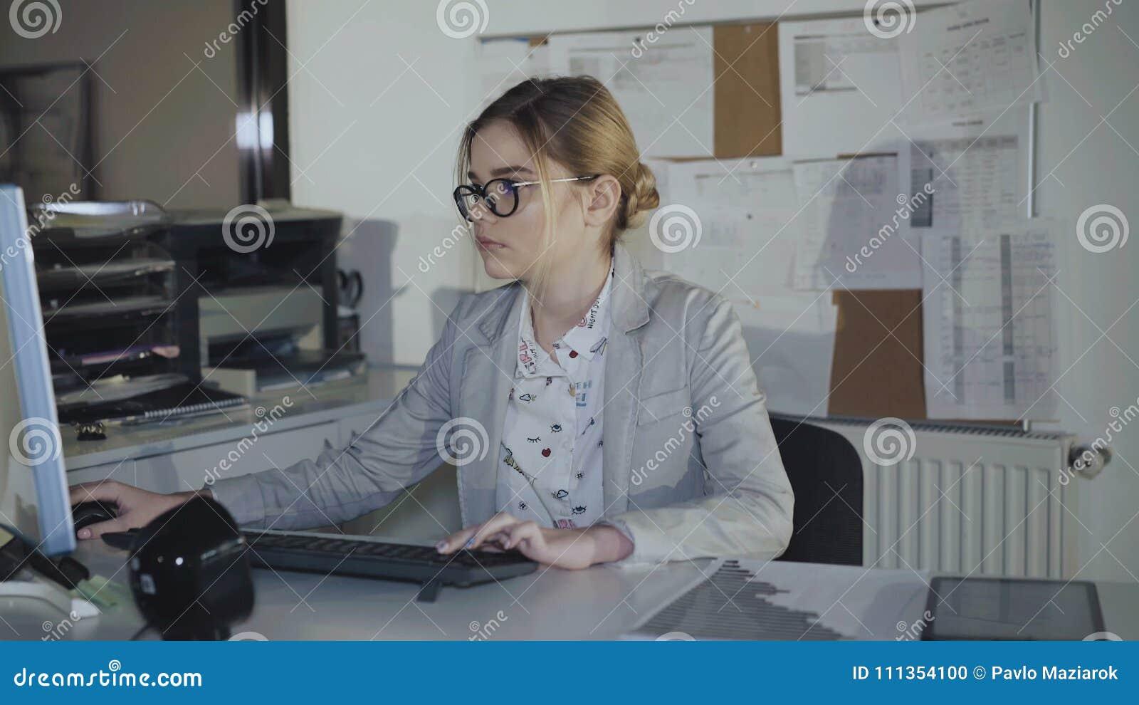 Ufficio K : La giovane segretaria in vetri lavora con il computer in ufficio