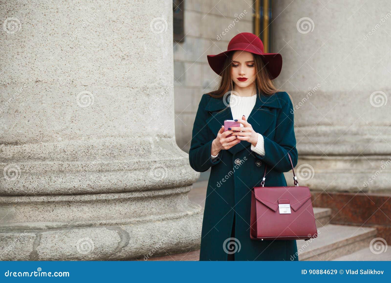 La giovane signora graziosa di modo porta il cappello ed il cappotto in smartphone classico di uso di stile