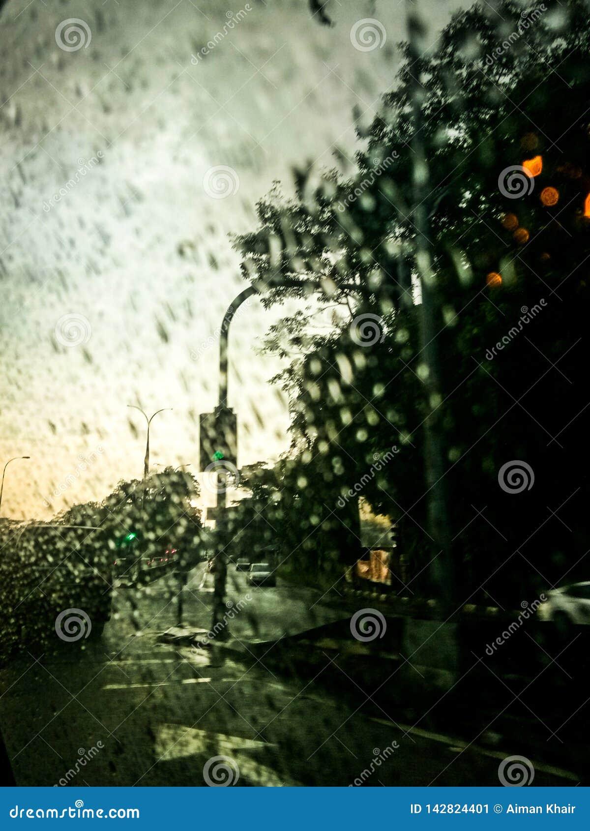 La gota de lluvia en la ventana en el interior de la ciudad del coche