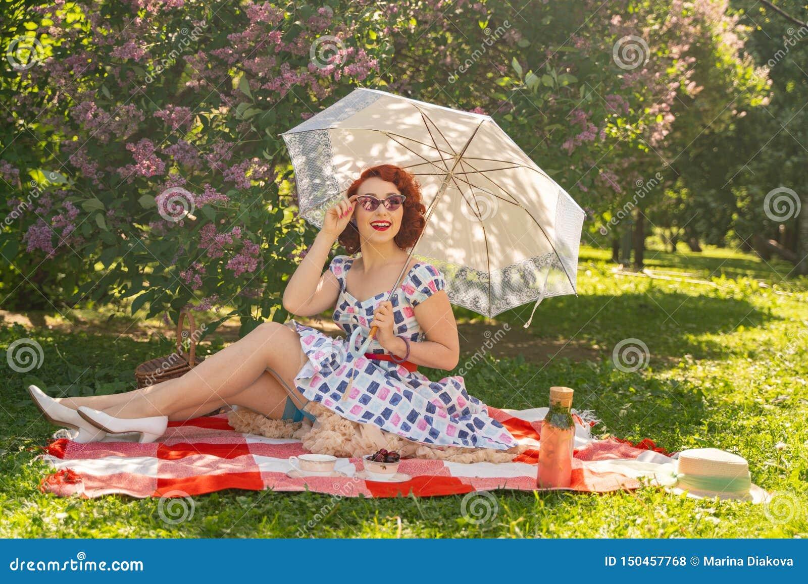 La goupille heureuse rousse vers le haut de la fille dans la robe d été de cru et des bas classiques avec une couture dans le dos