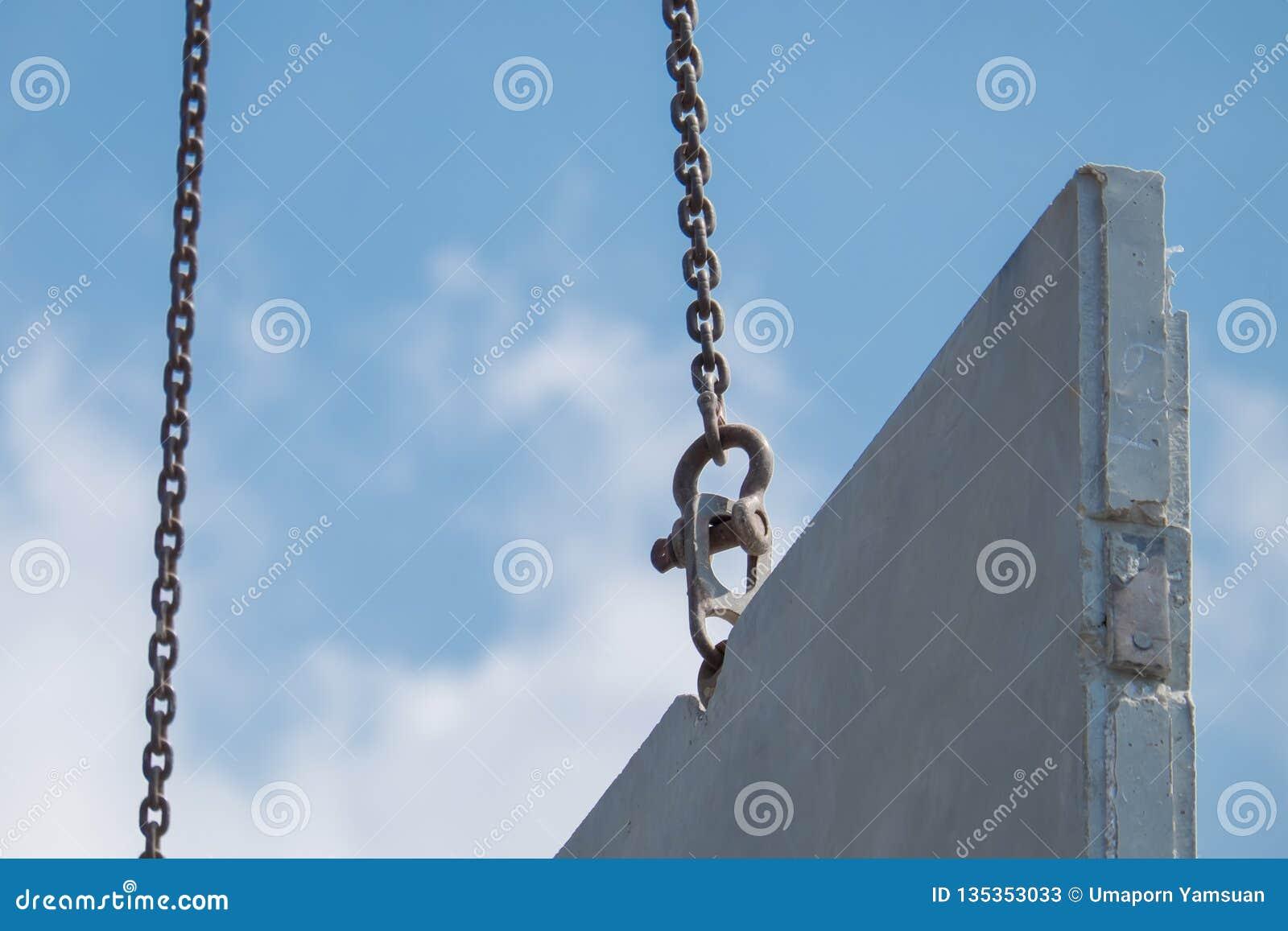 La grúa móvil levanta para arriba el muro de cemento prefabricado en nueva casa de la construcción