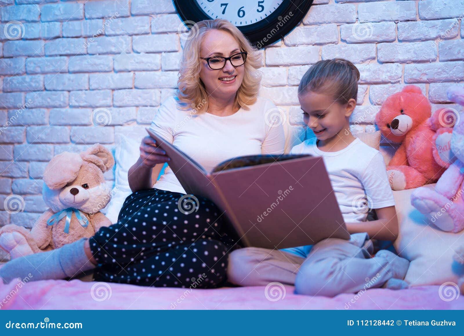 La grand-mère et la petite-fille lisent des contes de fées réservent la nuit à la maison