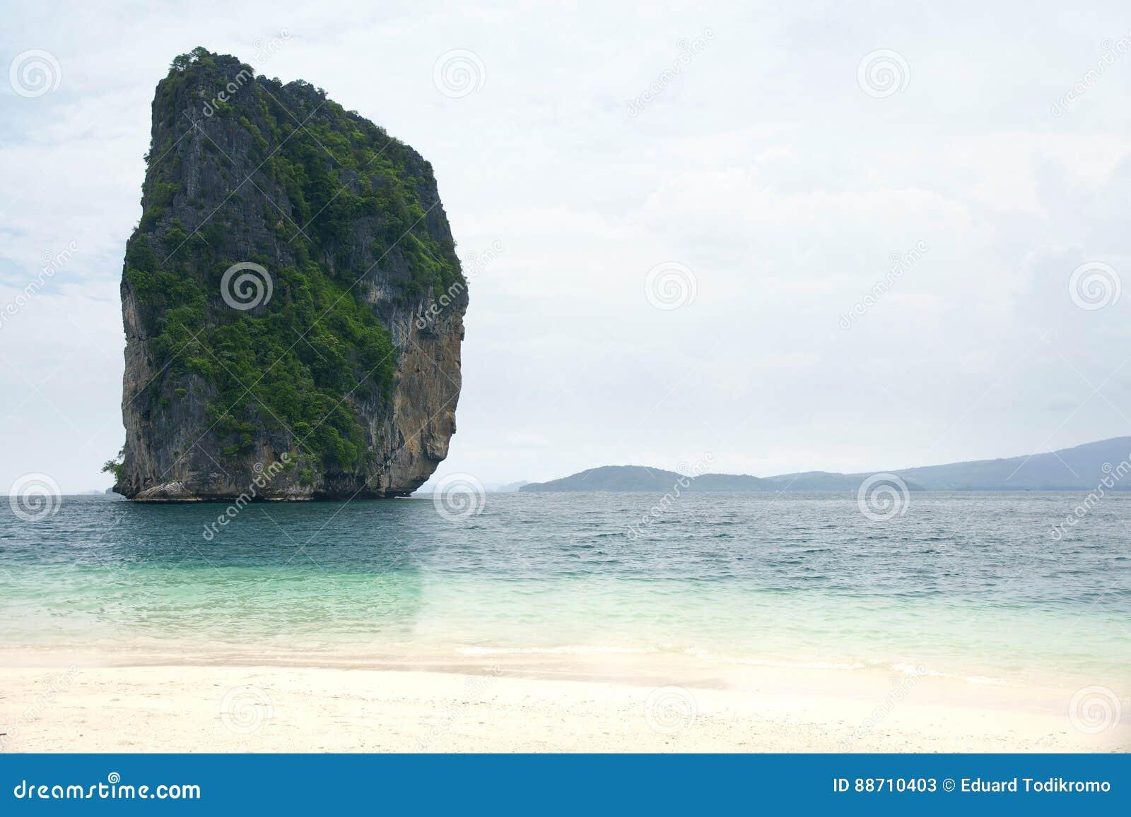 La grande alta scogliera della roccia riempita di vegetazione verde circondata dal blu di turchese ha colorato l acqua dell ocean