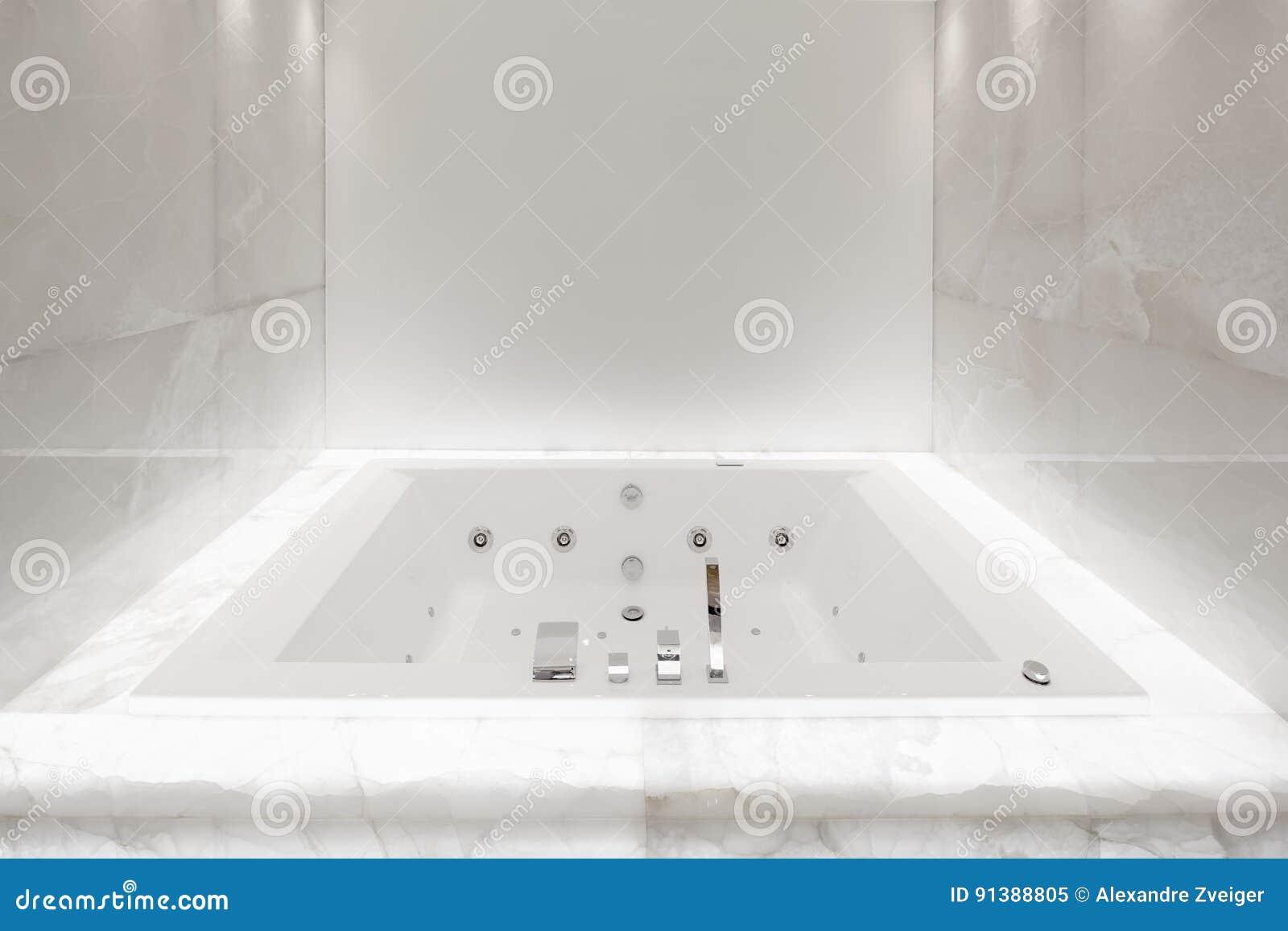 la grande baignoire dans la salle de bains a allumé le marbre