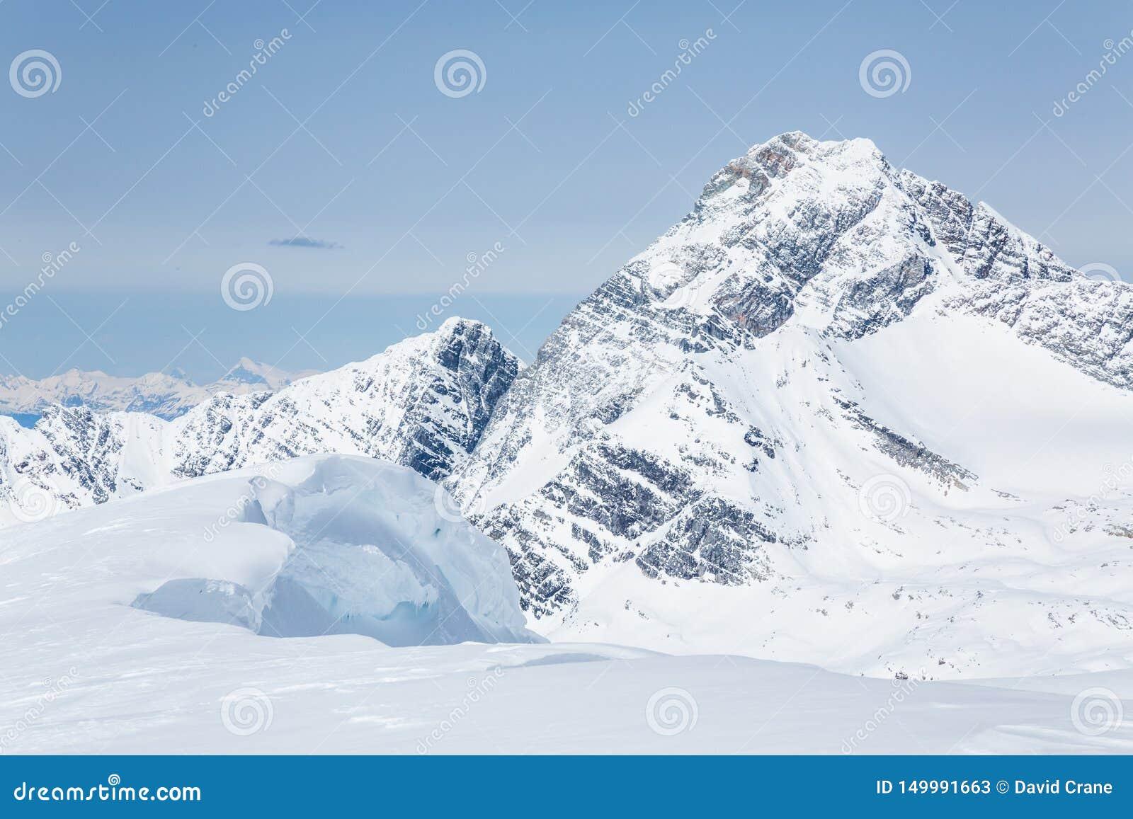 La grande corniche de la neige surplombante des jeunes font une pointe regarder le bâti Sir Donald