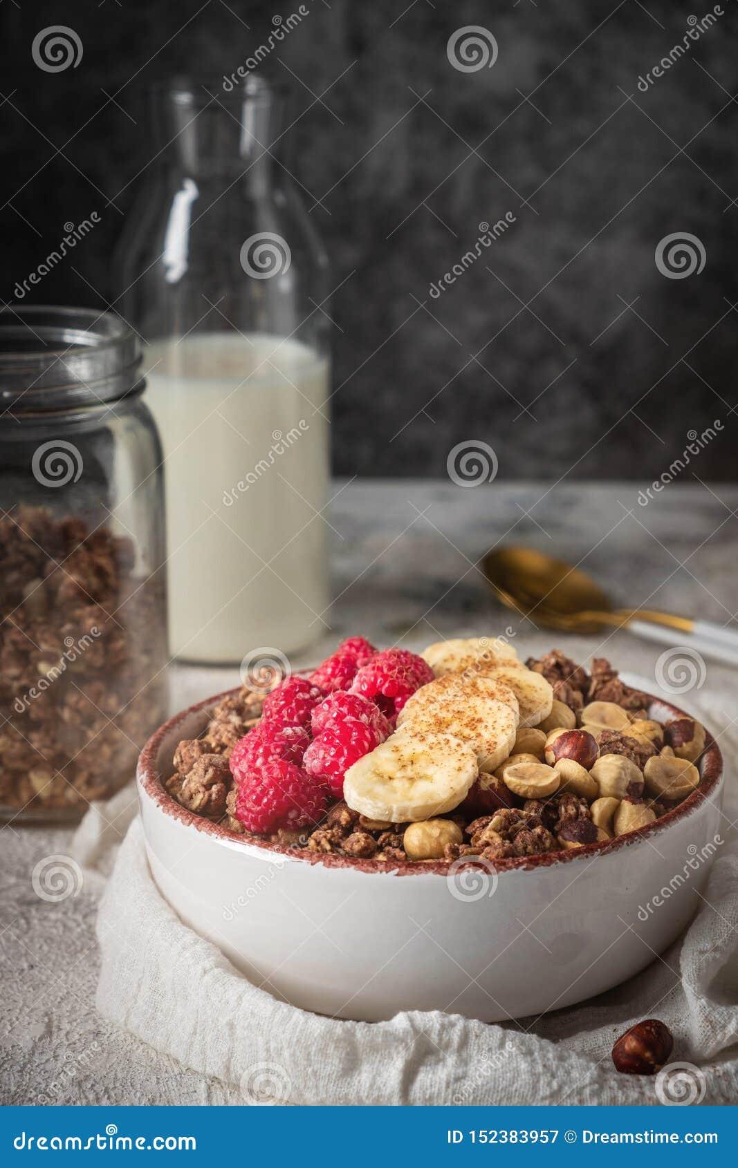 La granola saine de petit déjeuner dans un plat avec les écrous, la banane et les framboises, lait est versée d une bouteille