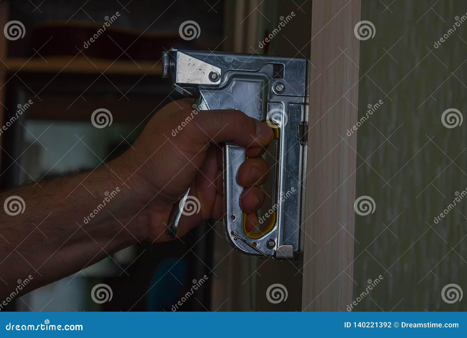 La grapadora de la construcción en una mano