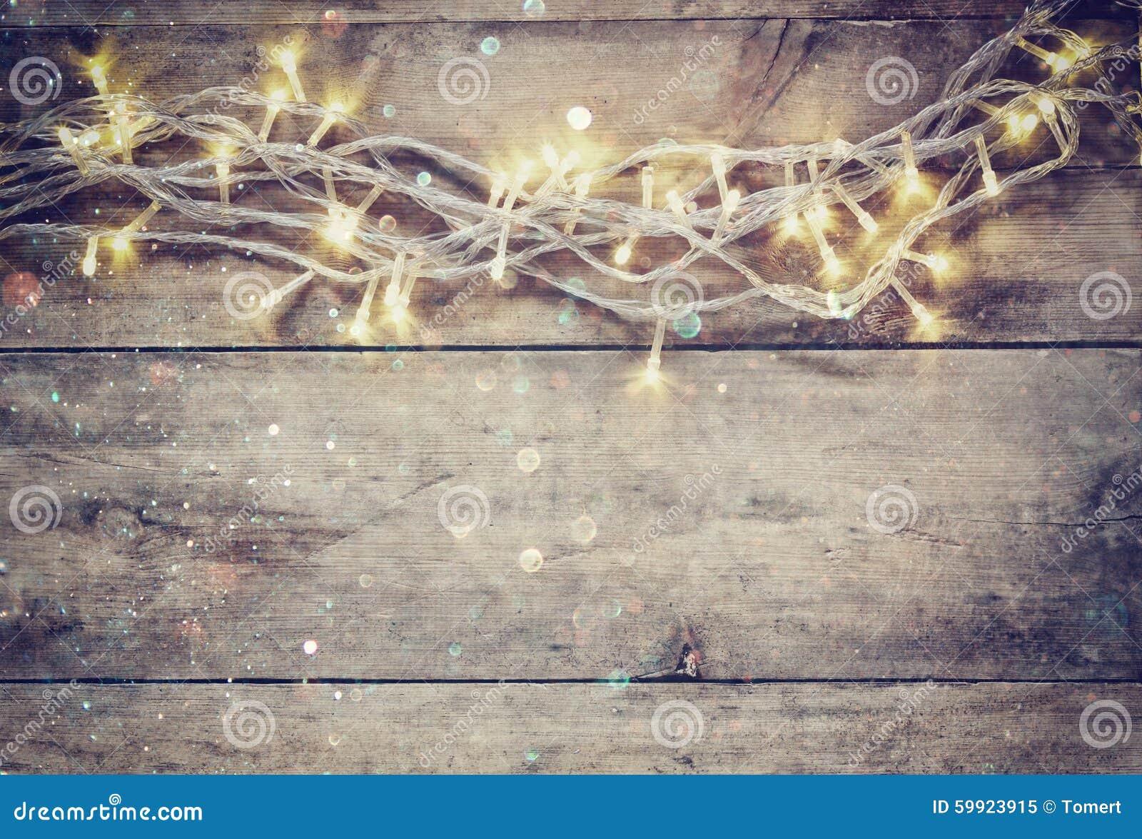 La guirnalda caliente del oro de la Navidad se enciende en fondo rústico de madera imagen filtrada con la capa del brillo