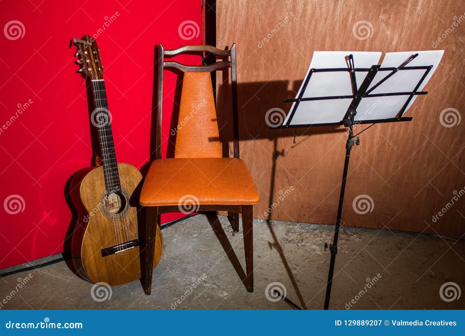 La guitare, la chaise et le lutrin ont montré dans un bas environnement de studio de budget