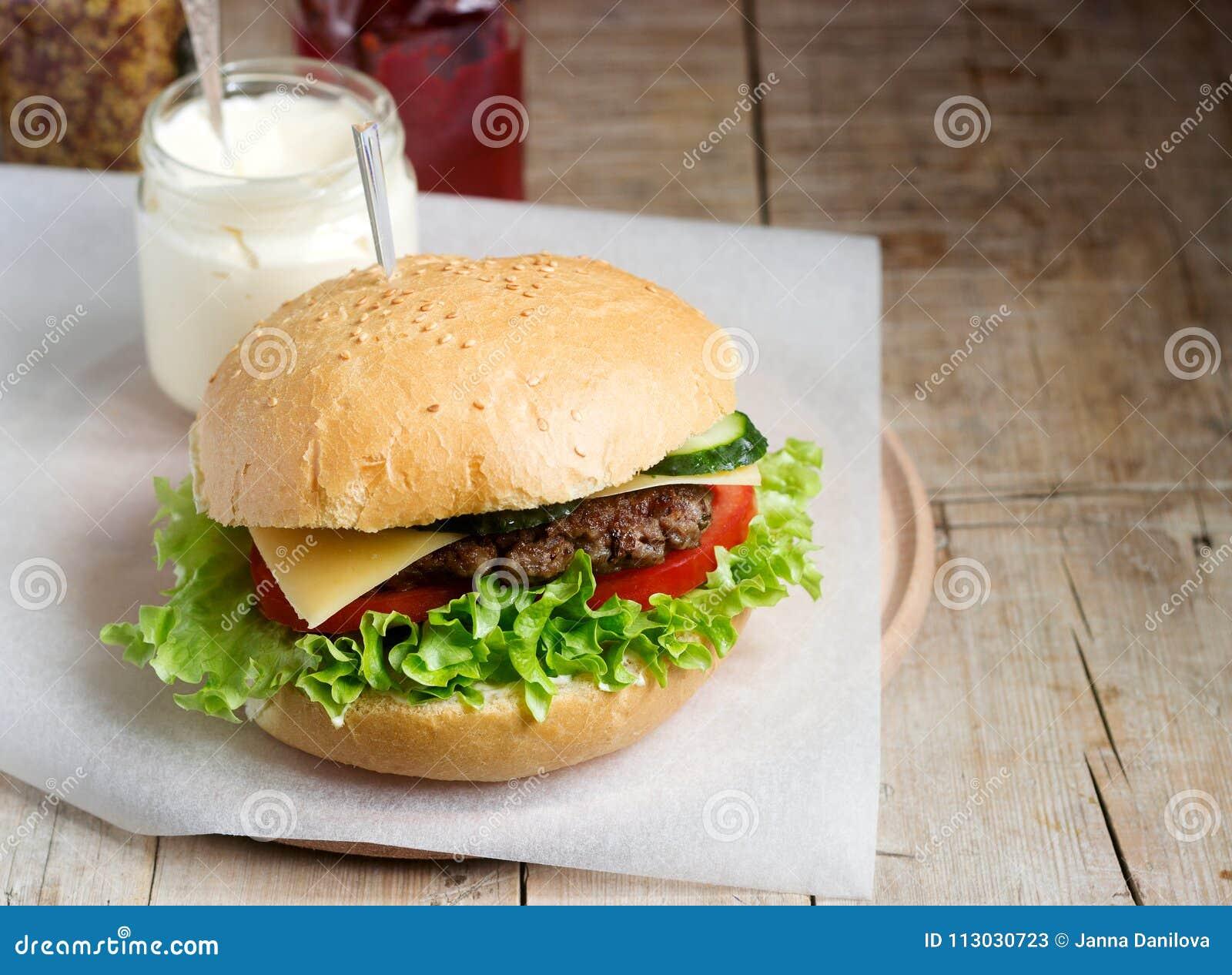 La hamburguesa hecha en casa con las verduras frescas sirvió con las diversas salsas