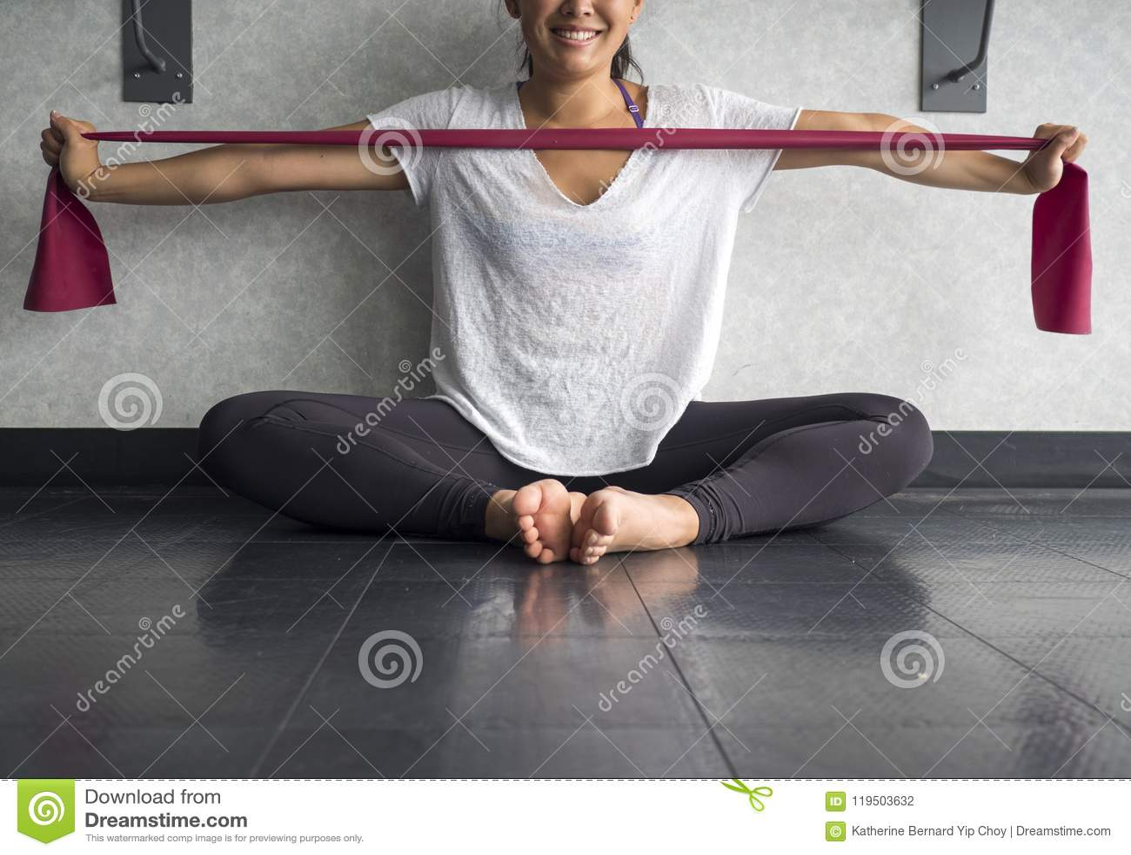 La hembra activa joven sonriente que usa un theraband ejercita la banda para consolidar sus músculos de los brazos en el estudio