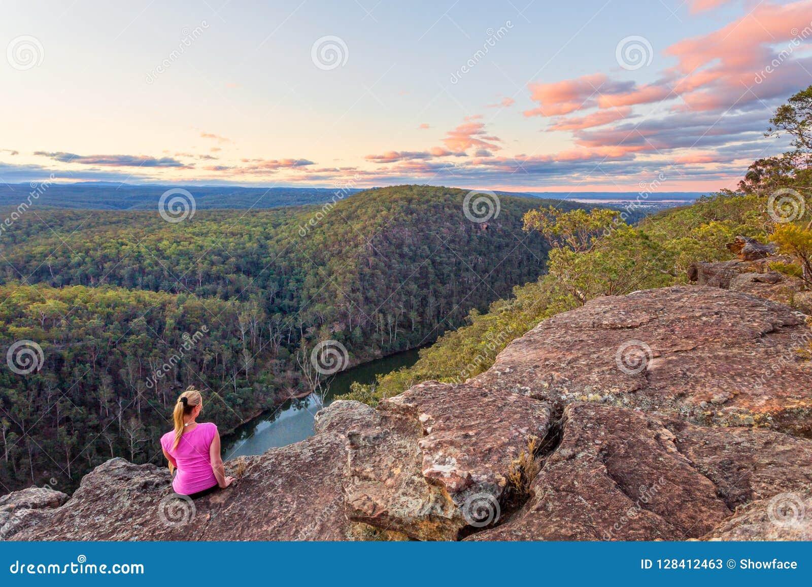 La hembra sienta la roca con opiniones sobre el río de Nepean y las montañas azules