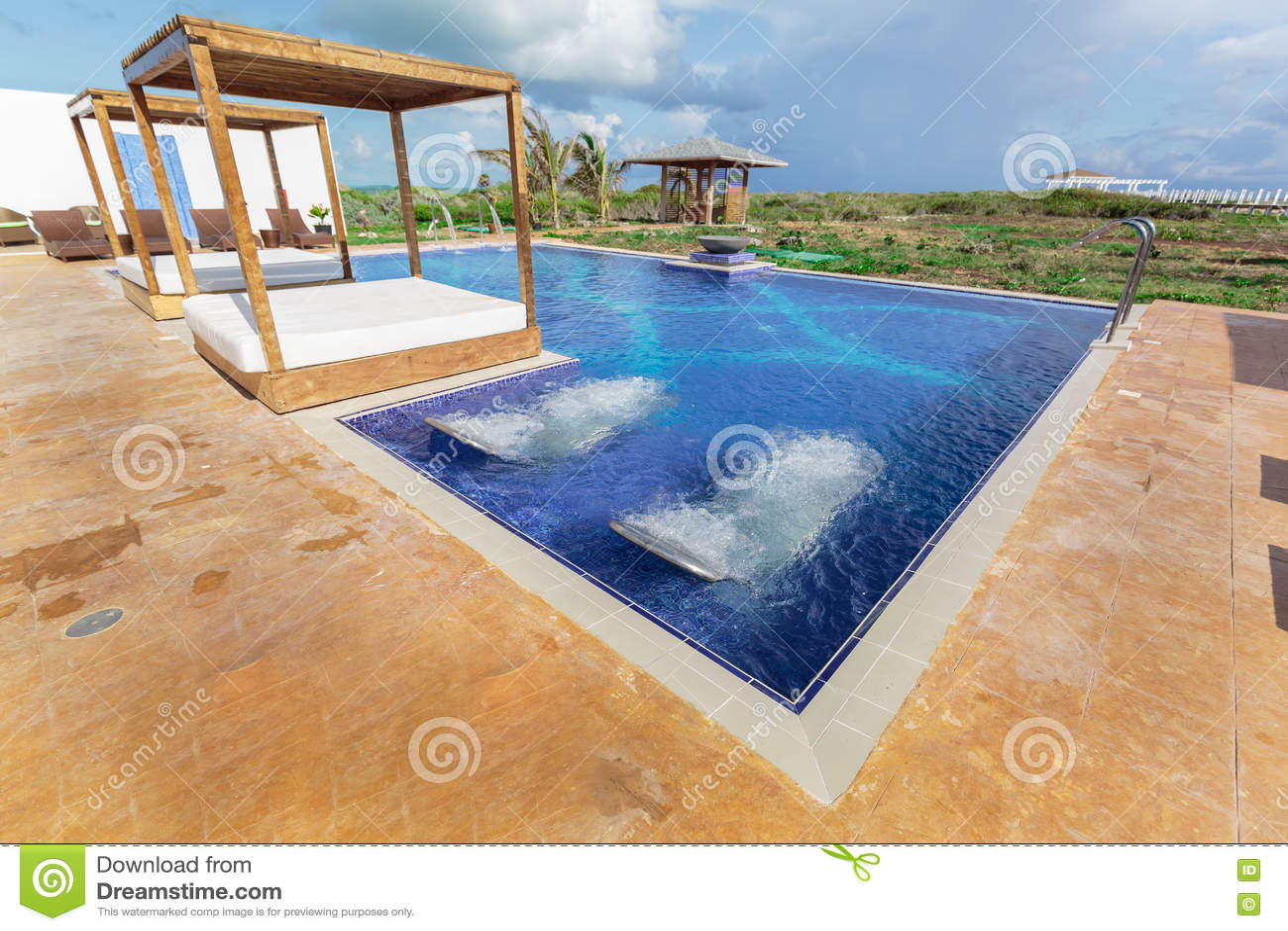 La hermosa vista de invitación que sorprende del balneario del centro turístico y la piscina con aguamarina dan masajes a camas