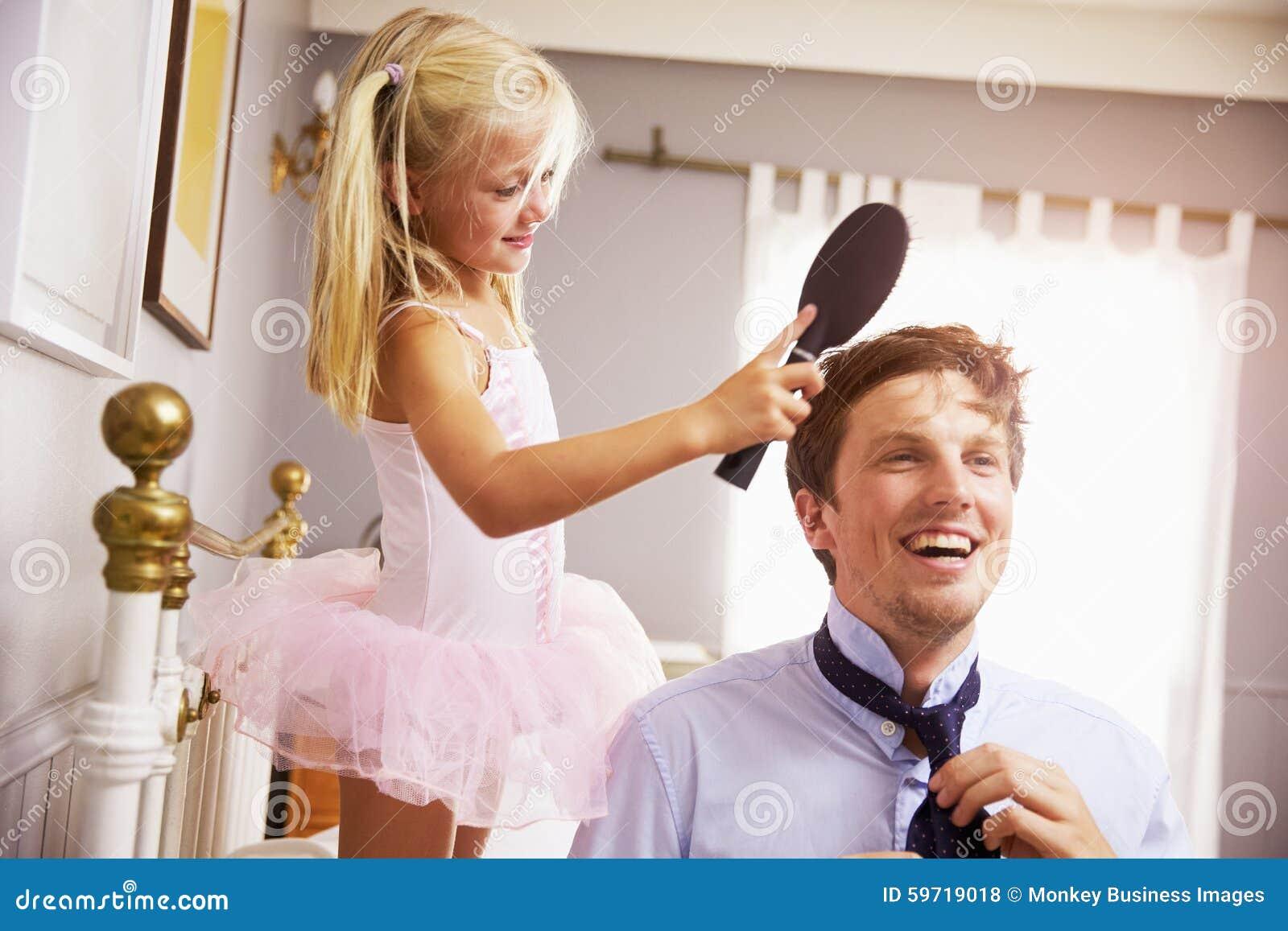 La hija ayuda al padre To Get Ready para el trabajo con el pelo del cepillo