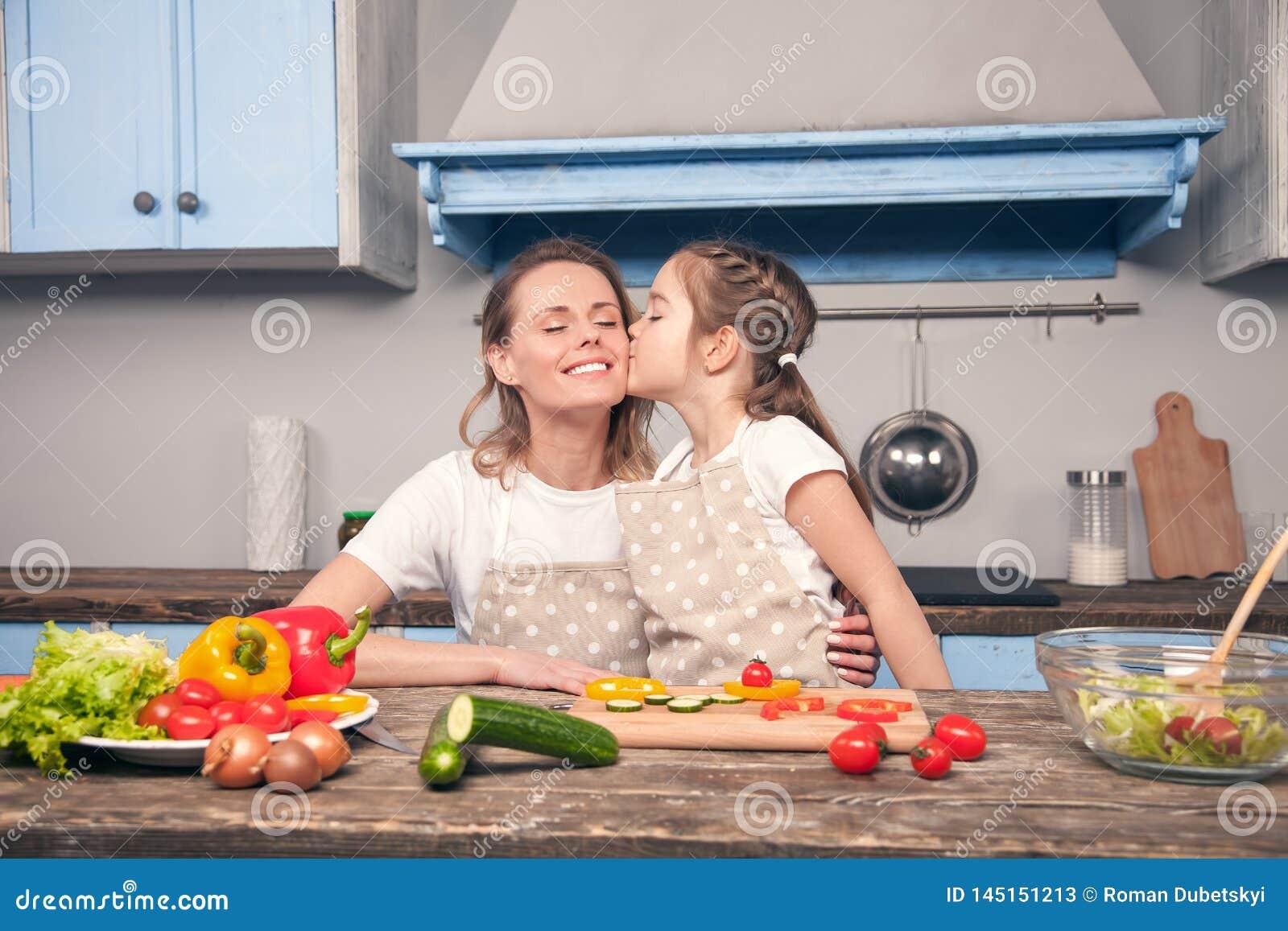 La hija linda besa a la mamá en su mejilla mientras que cocina en una cocina azul hermosa