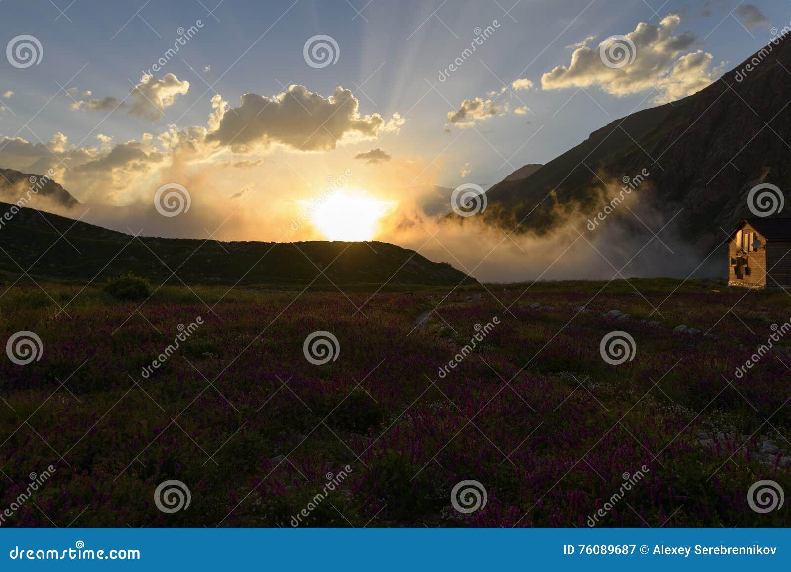 La hutte de montagne sur le champ se développant en soleil rayonne au coucher du soleil