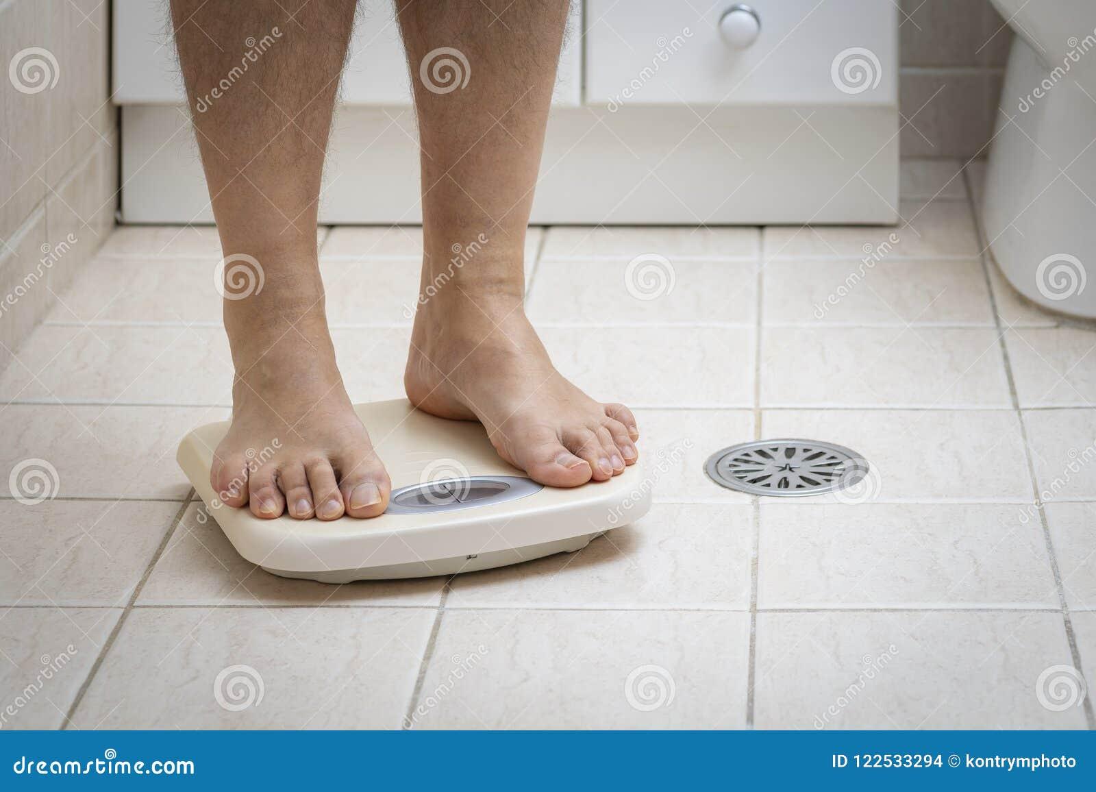 La imagen cosechada de los pies del hombre que se colocan encendido pesa la escala