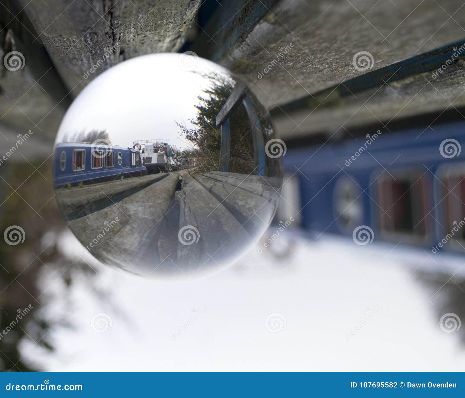 La imagen de los barcos amarrados a lo largo del canal se refractó a través de la bola de cristal