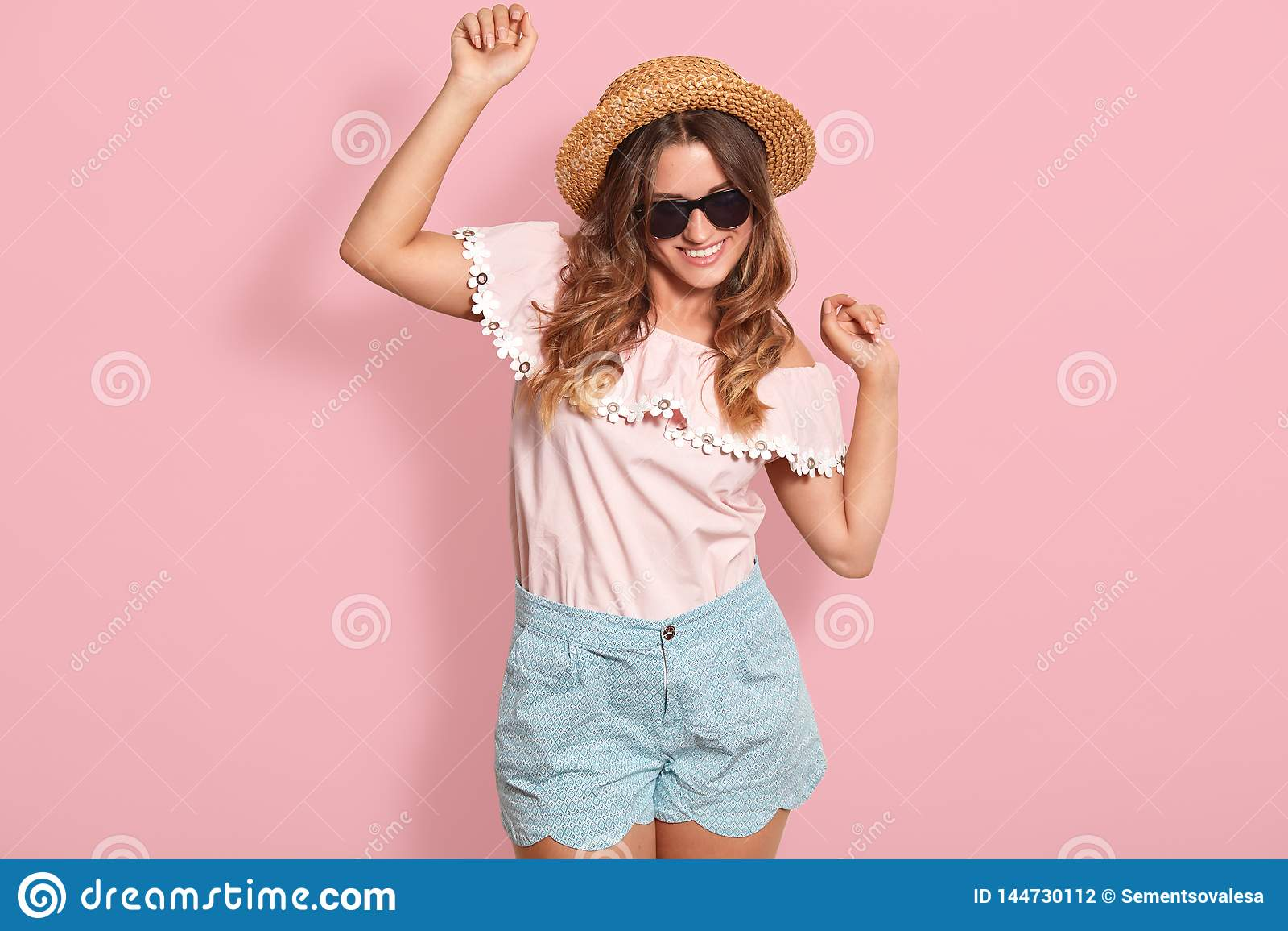 La imagen de la muchacha cabelluda oscura joven con el baile satisfecho de la expresión de la cara en fondo color de rosa, escuc