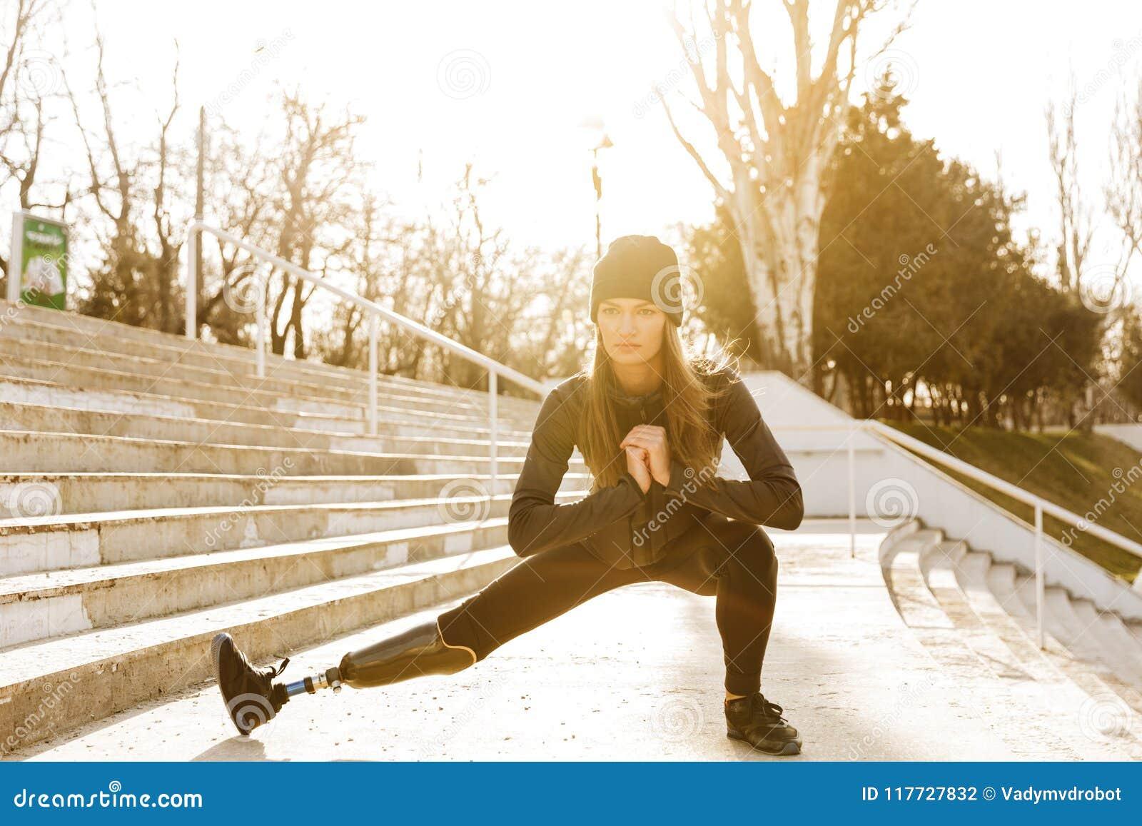 La imagen de la muchacha corriente discapacitada en ropa de deportes, haciendo se sienta sube y