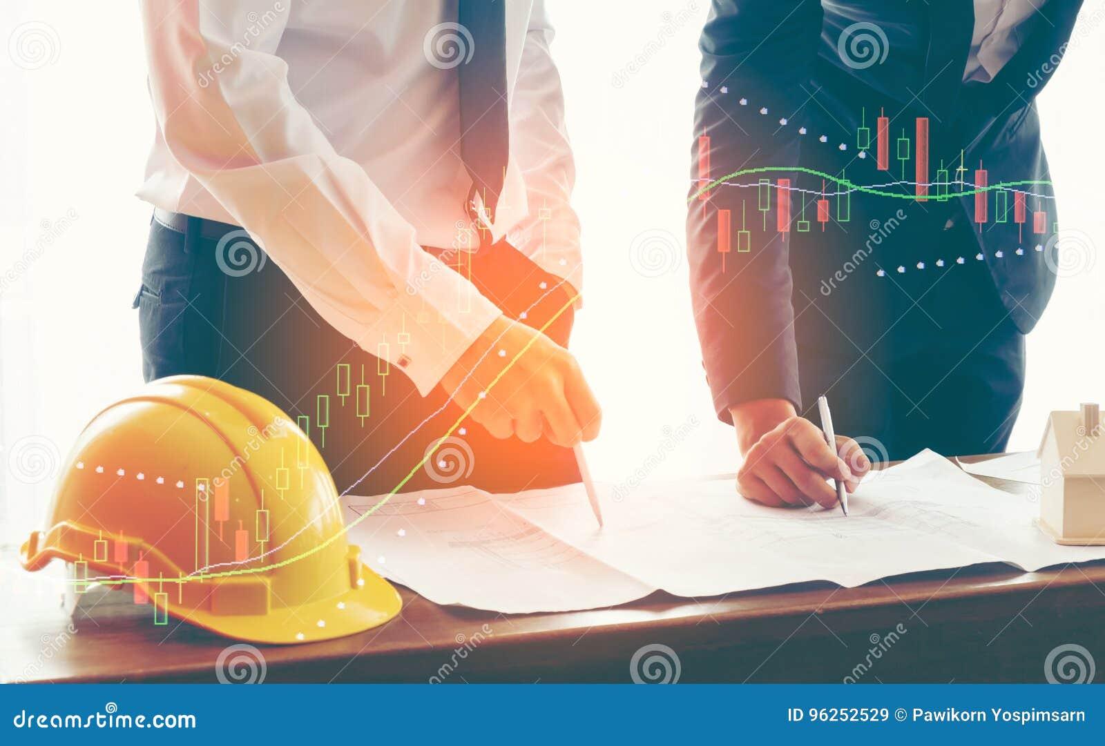 La imagen del hombre de negocios dos o el ingeniero discute el documento del informe de la carta de la venta sobre la tabla