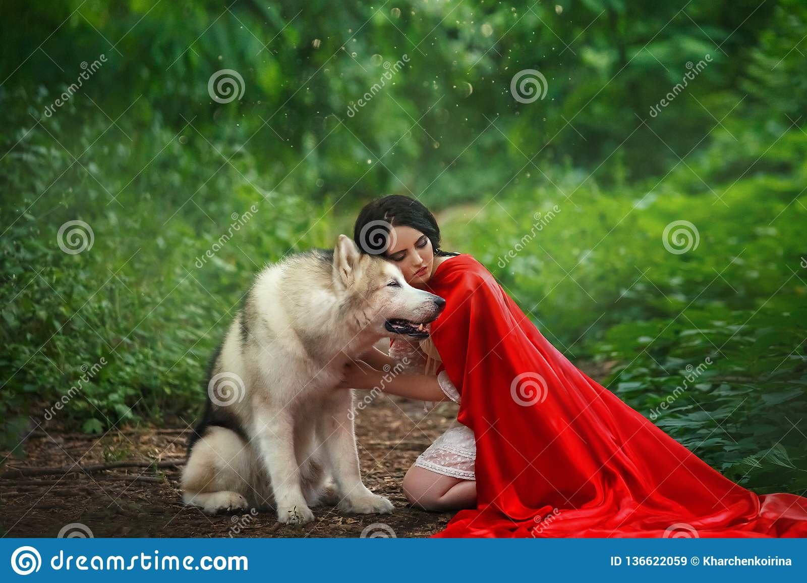 La imagen fabulosa, señora atractiva morena oscuro-cabelluda en vestido blanco corto, capa roja larga del escarlata que miente en