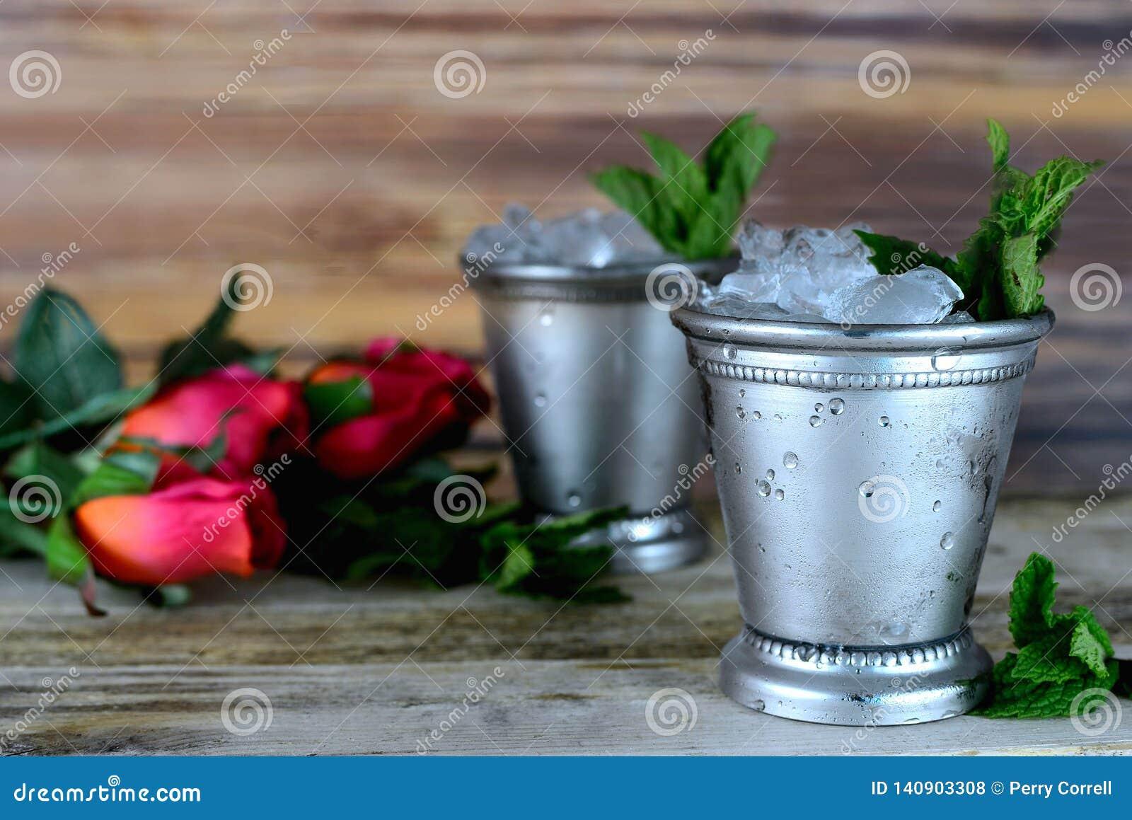 La imagen para Kentucky derby en mayo que muestra a dos la plata acuña las tazas de la julepe con hielo y la menta fresca machaca