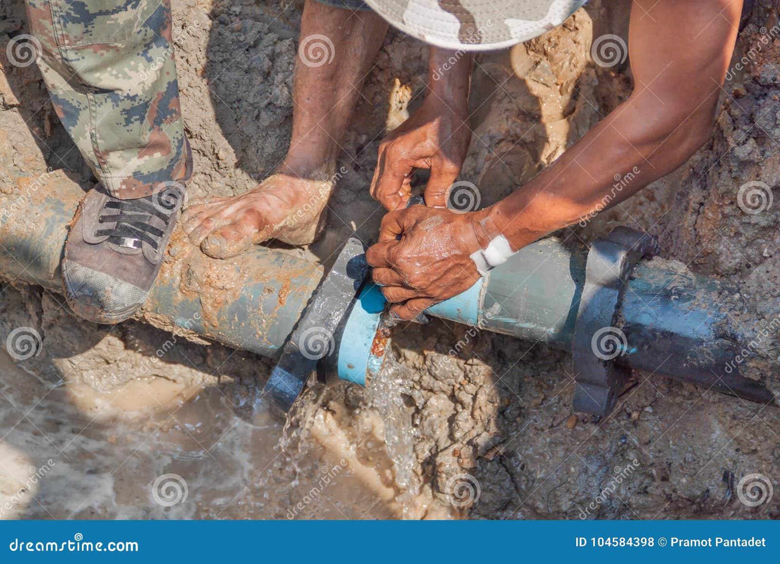 La jambe de réparation de travailleurs frappent du pied sur mettre d aplomb cassée pour trouer la fuite de l eau de difficulté à