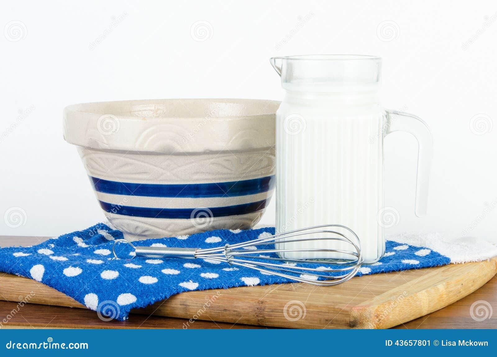 La jarra agradable de leche con el cuenco y bate