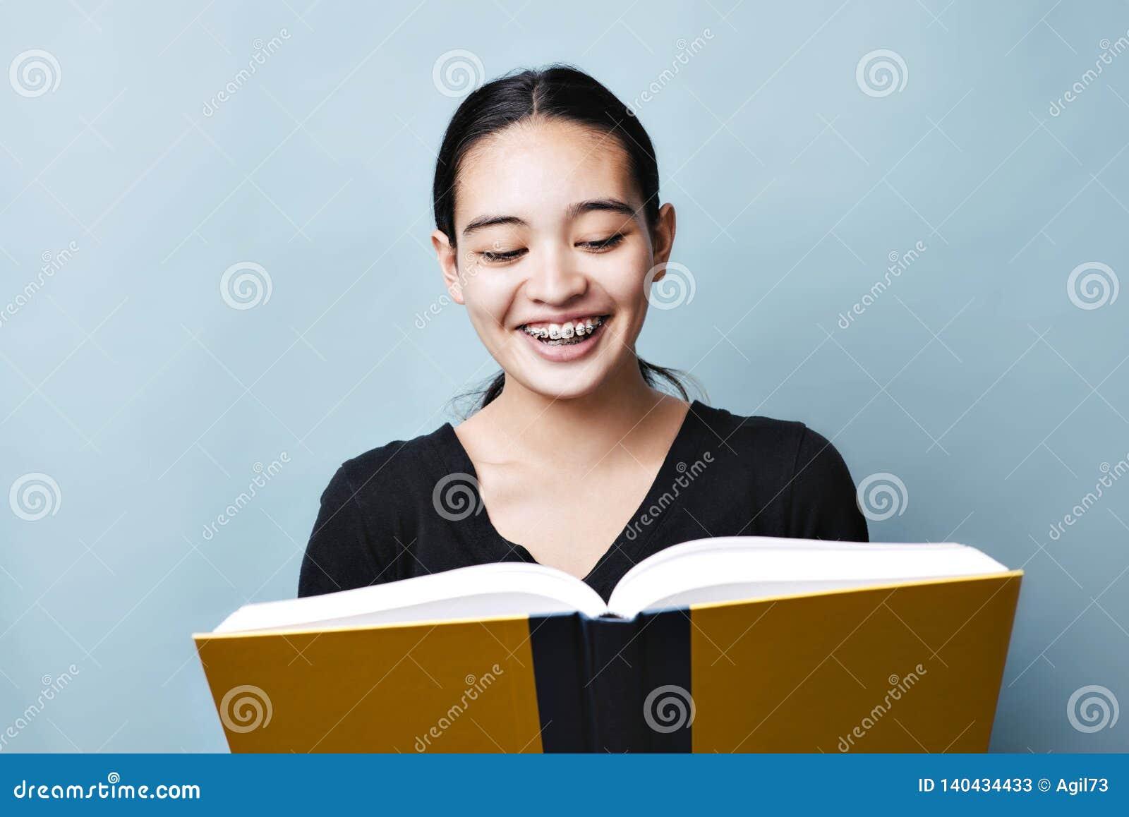La jeune adolescente lit du manuel et sourit expression heureuse de Lauging
